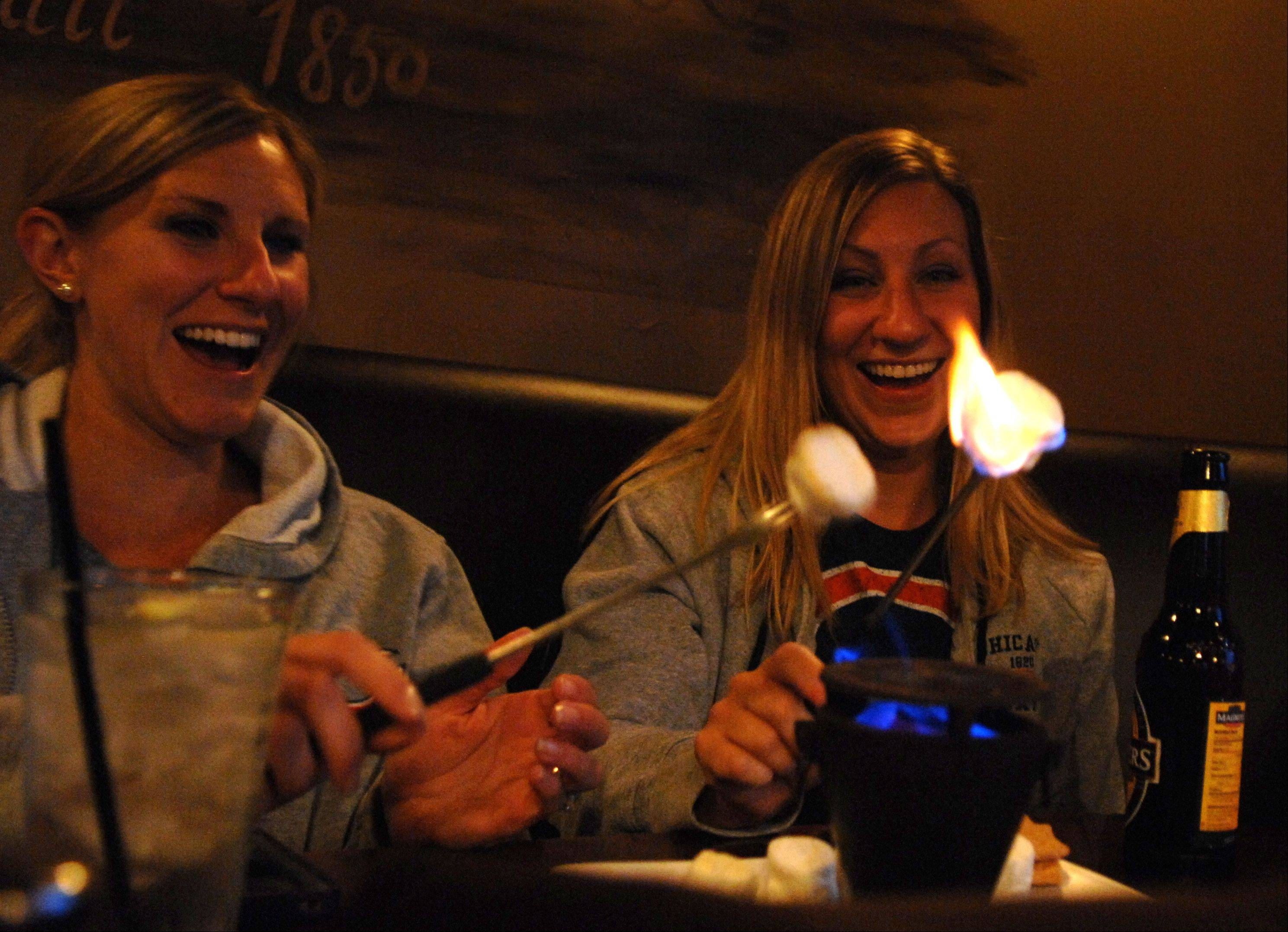 Danielle Weyant, left, and Lindsay Sorci, both of St. Charles, set their marshmallows aflame after ordering the s'mores for dessert at The Office in St. Charles.
