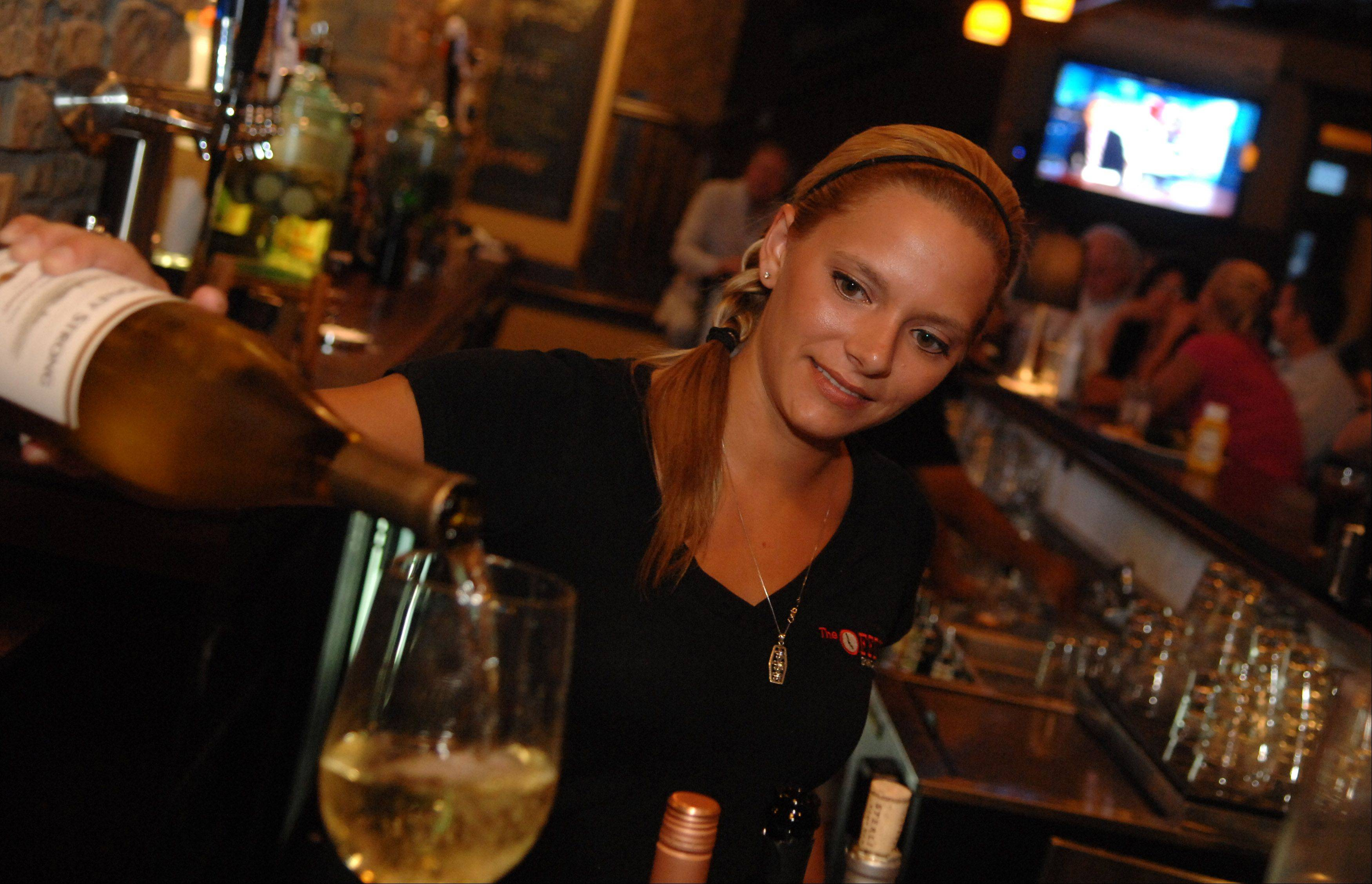 Bartender Stephanie Miller pours a glass of wine at The Office.