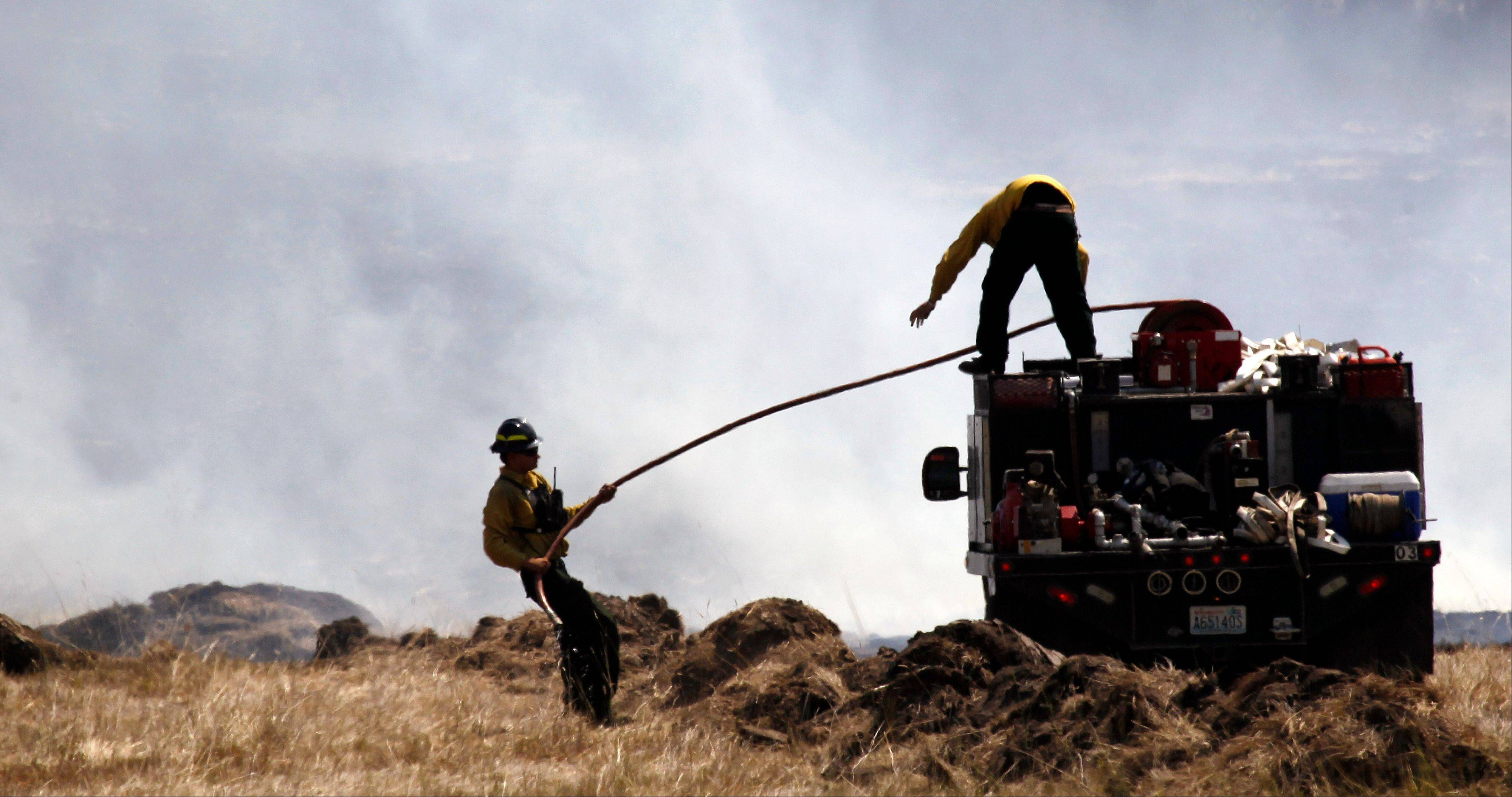 Firefighters pull a hose into position to quench a smoldering field Wednesday near Cle Elum, Wash.