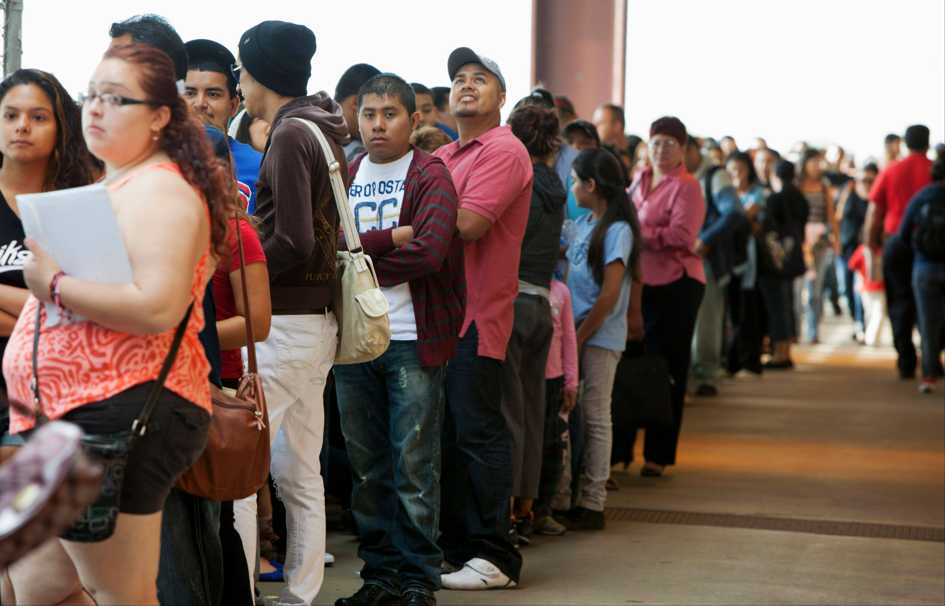 Young immigrants stand in a long line at Chicago's Navy Pier on Wednesday, waiting for guidance on a new federal program that would help them work legally in the United States and avoid deportation.