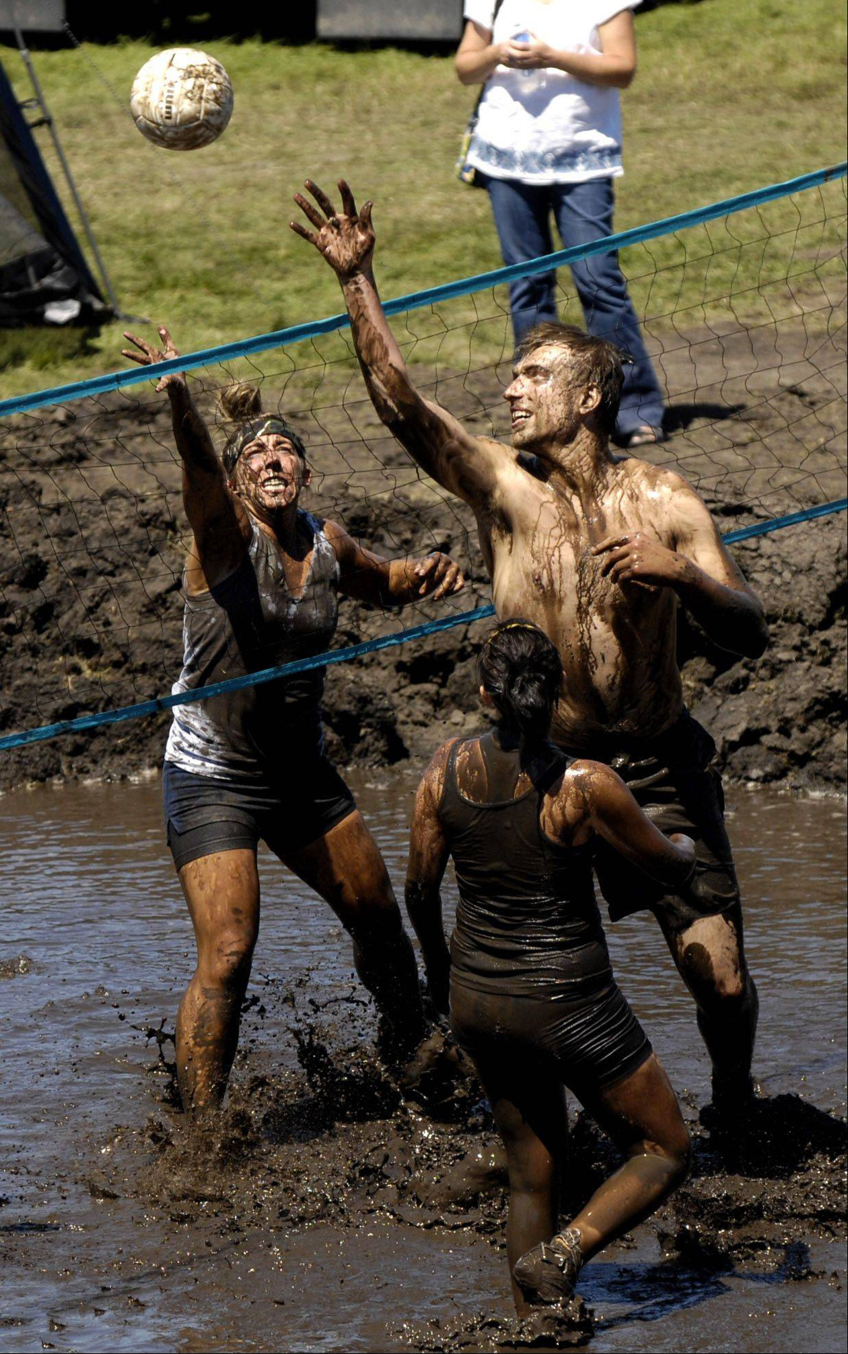 Mud volleyball players Jeff Klosinski and Heather Cornell, right, play on the final day of last year's Elburn Days at Lions Park.