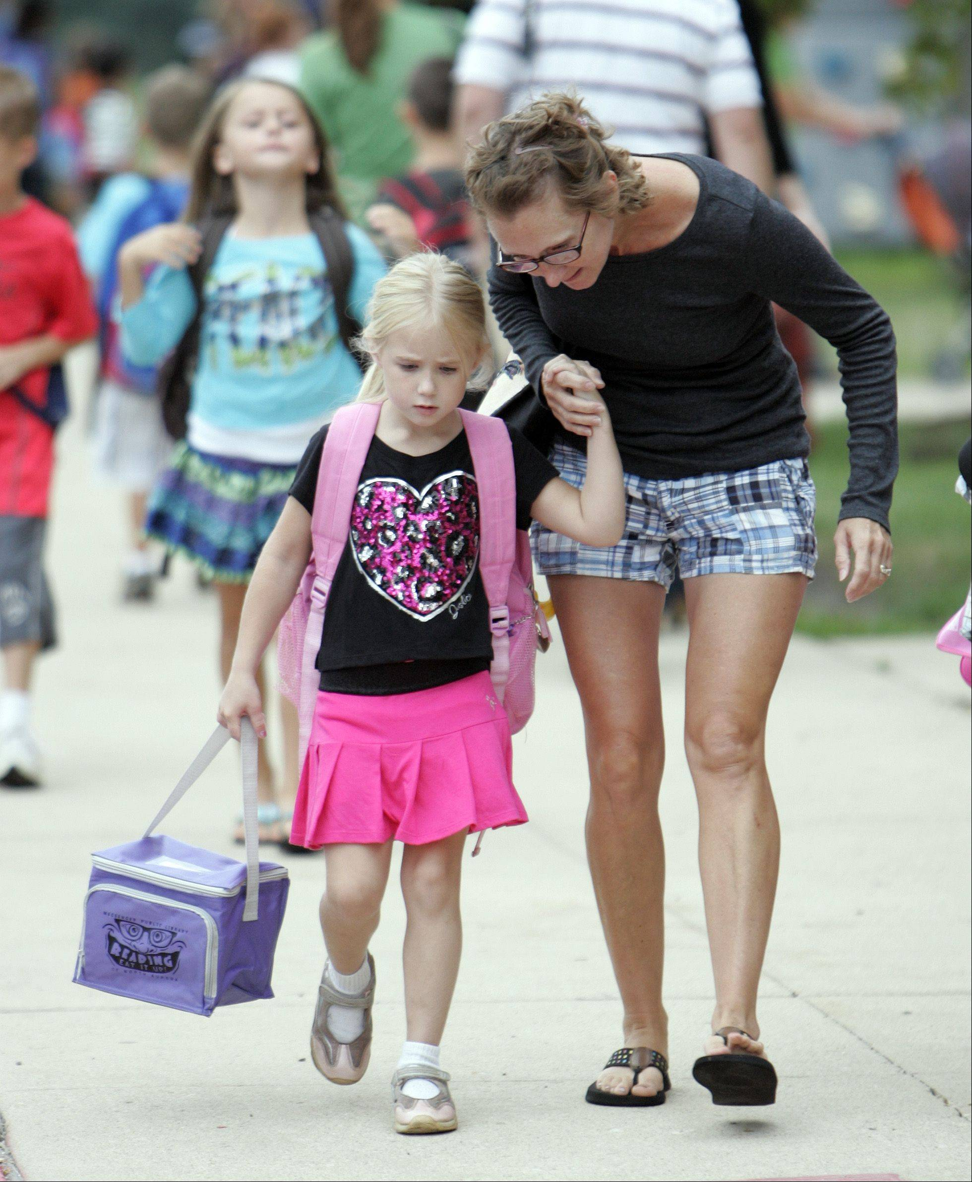 Debbie Whitlock of North Aurora, walks her daughter Abby, 5, to kindergarten during the first day of school at Fearn Elementary School in North Aurora Wednesday.