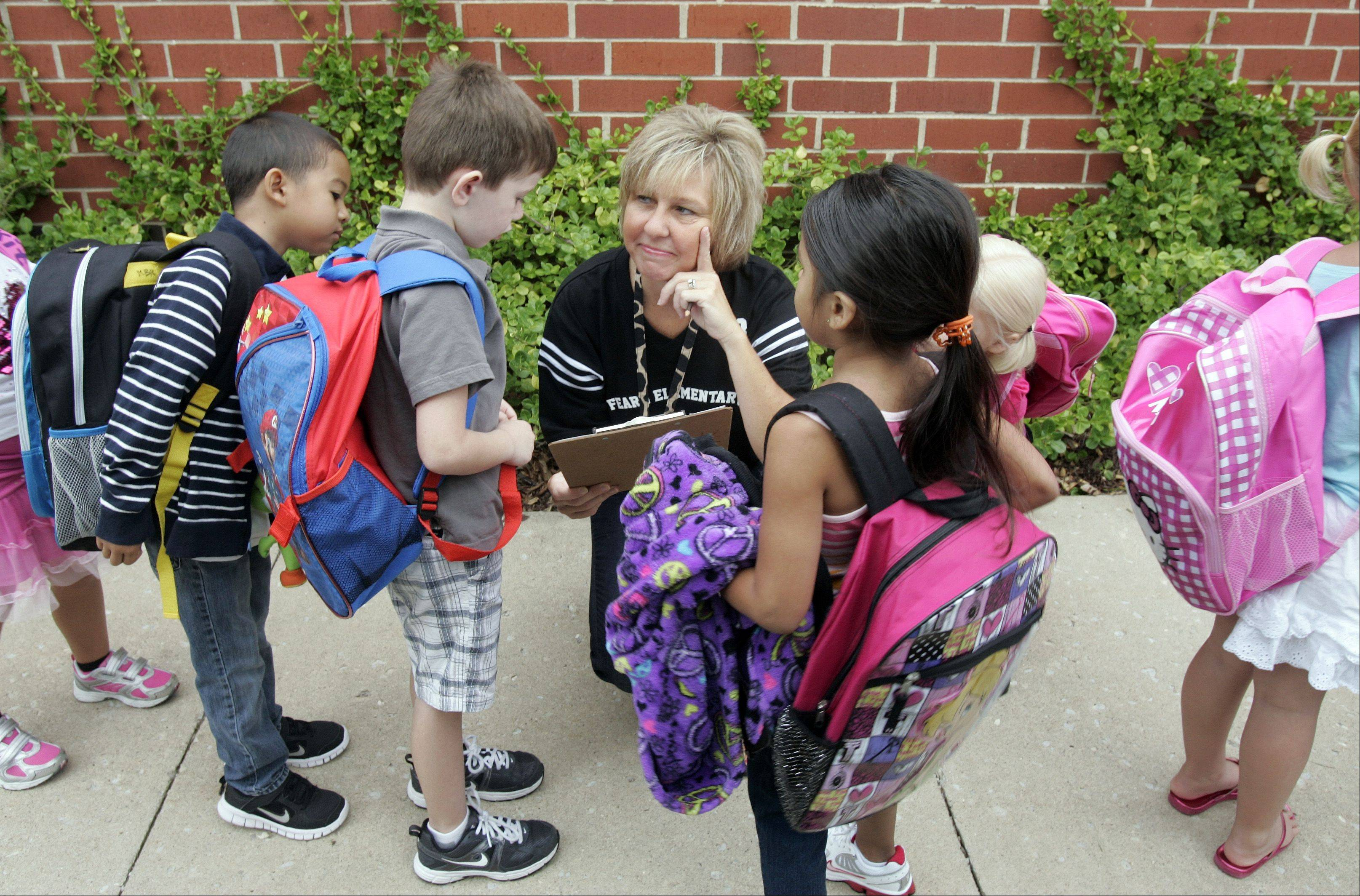 Kindergarten teacher Tricia Brummel greets her students at Fearn Elementary School in North Aurora Wednesday.