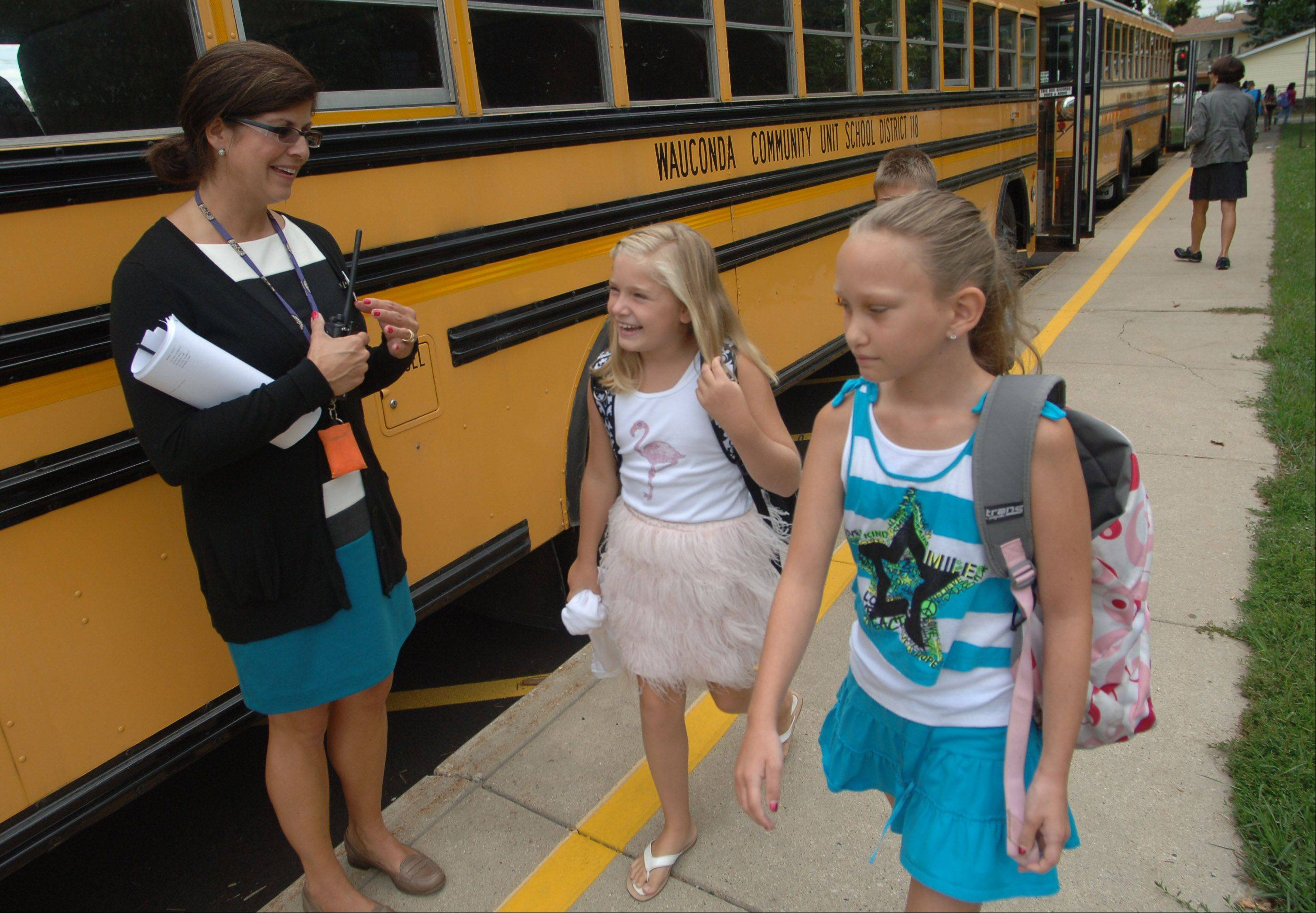 Robert Crown School principal Karrie Diol, left, greets students as they get off the bus in Wauconda Wednesday morning.