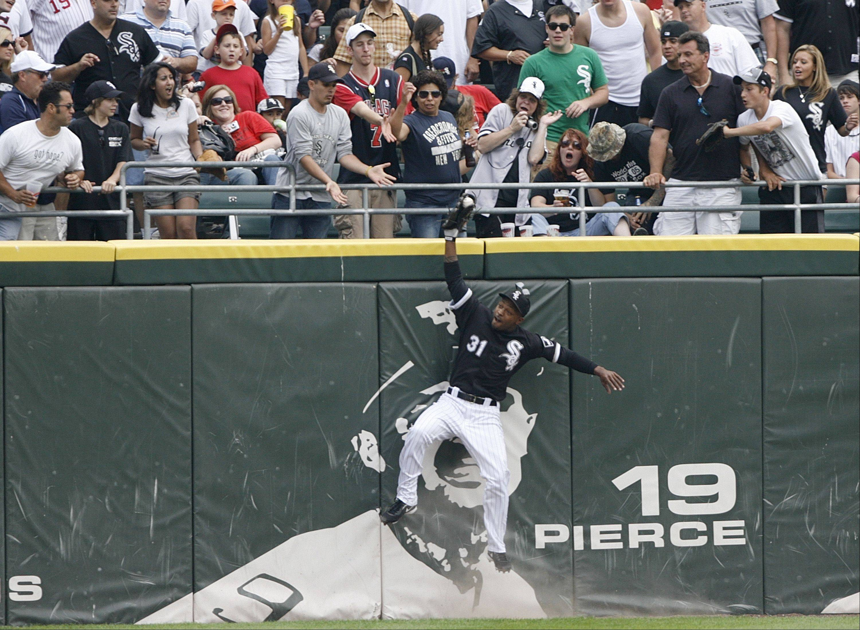 White Sox center fielder Dewayne Wise falls into the wall as he catches a deep fly hit by the Tampa Bay Rays Gabe Kapler during the ninth inning. Mark Buehrle threw a perfect game in the White Sox' 5-0 win.