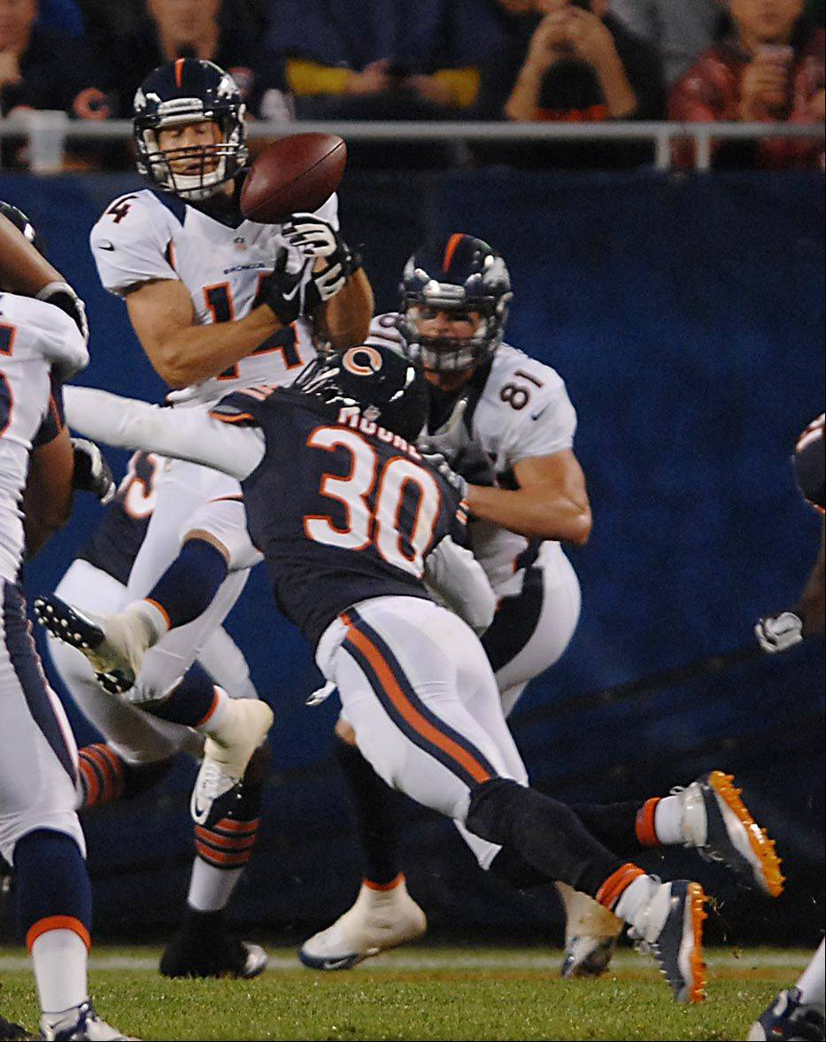 Chicago Bears defensive back D.J. Moore knocks the ball out of the hands of Denver Broncos wide receiver Brandon Stokley Thursday night in the first preseason game at Soldier Field in Chicago.