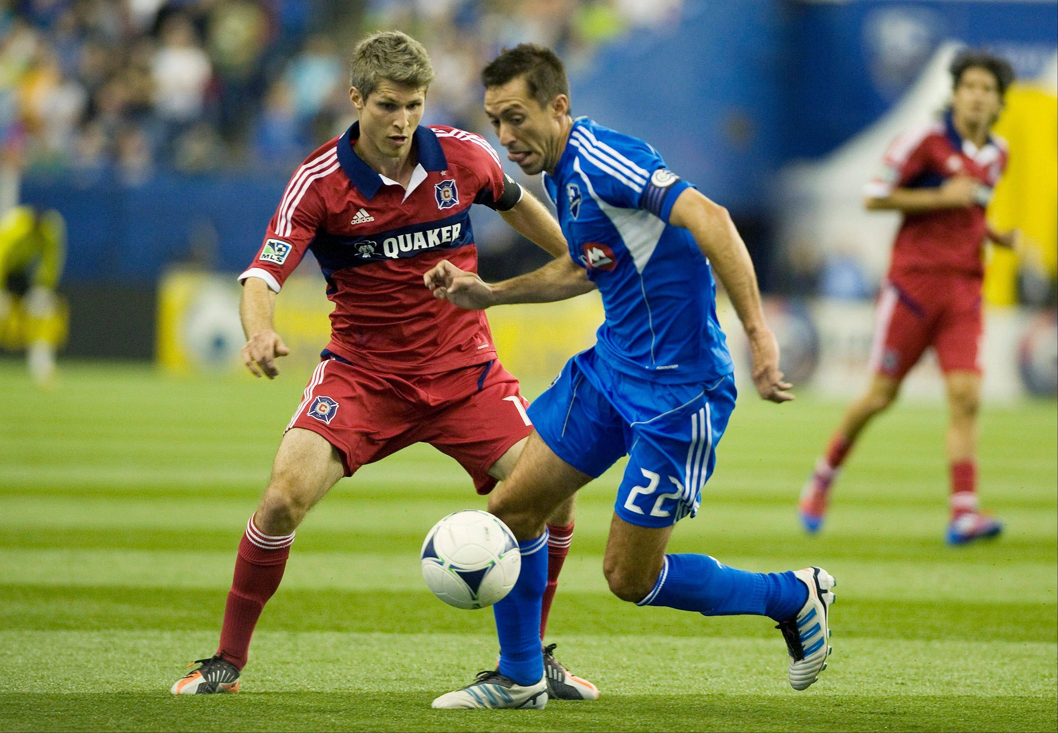 Montreal Impact's Davy Arnaud (22) shields the ball from Chicago Fire's Logan Pause during first half MLS soccer action in Montreal, Saturday, March 17, 2012.