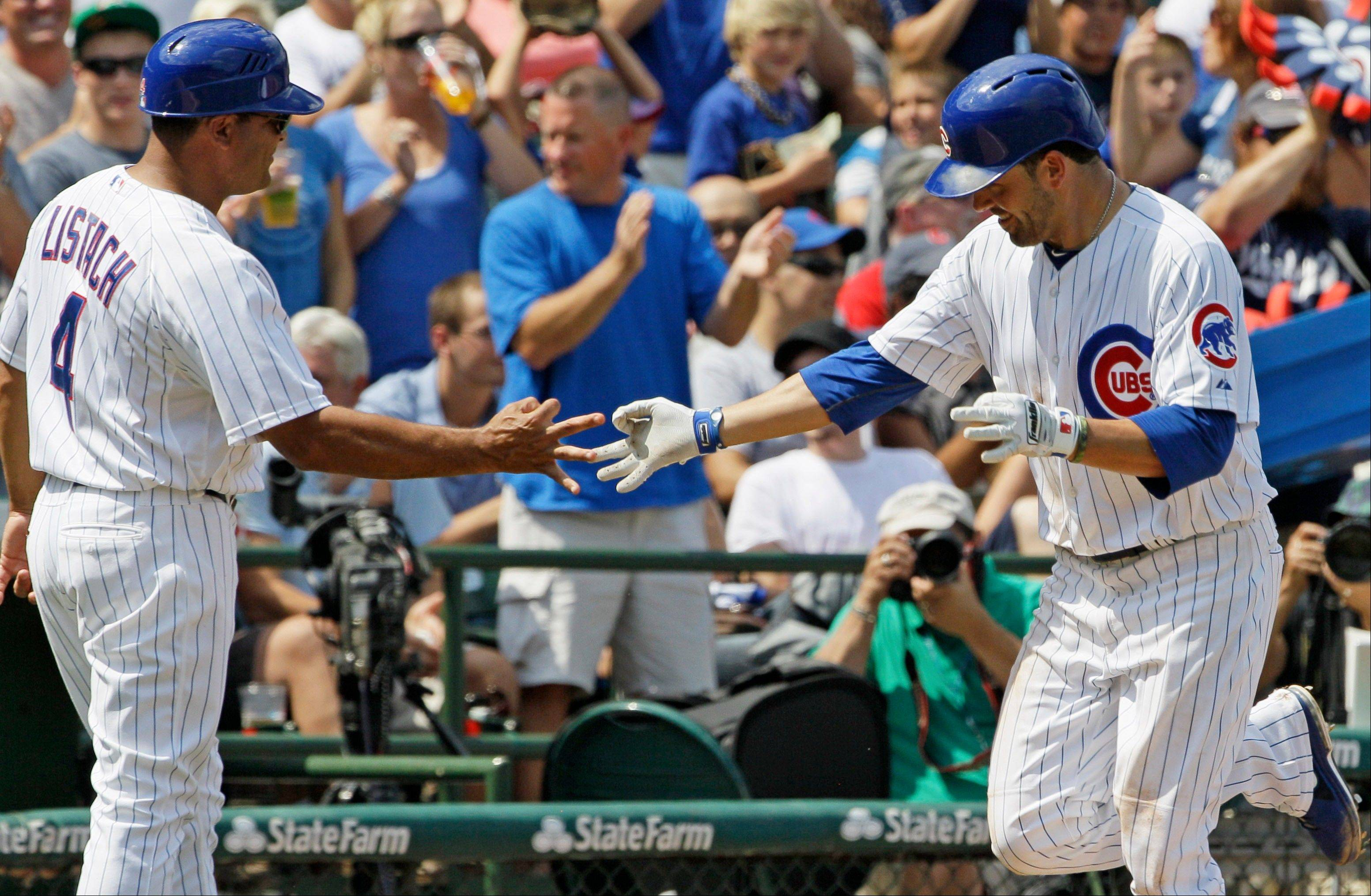 Cubs outfielder David DeJesus, right, celebrates with third base coach Pat Listach after hitting a solo home run Wednesday during the third inning against the Houston Astros.