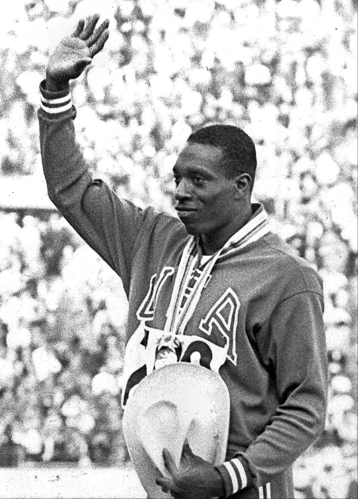 United States sprinter Bob Hayes waves to the crowd from the victory stand after winning the men's 100-meter dash finals at the 1964 Tokyo Summer Olympics. Hayes' gold medal in the 100 meters earned him the designation of the world's fastest human and provided him the opportunity to become the first Olympic champion to make it big in professional football as a wide receiver for nine years with the Dallas Cowboys, and a two-time All-Pro.