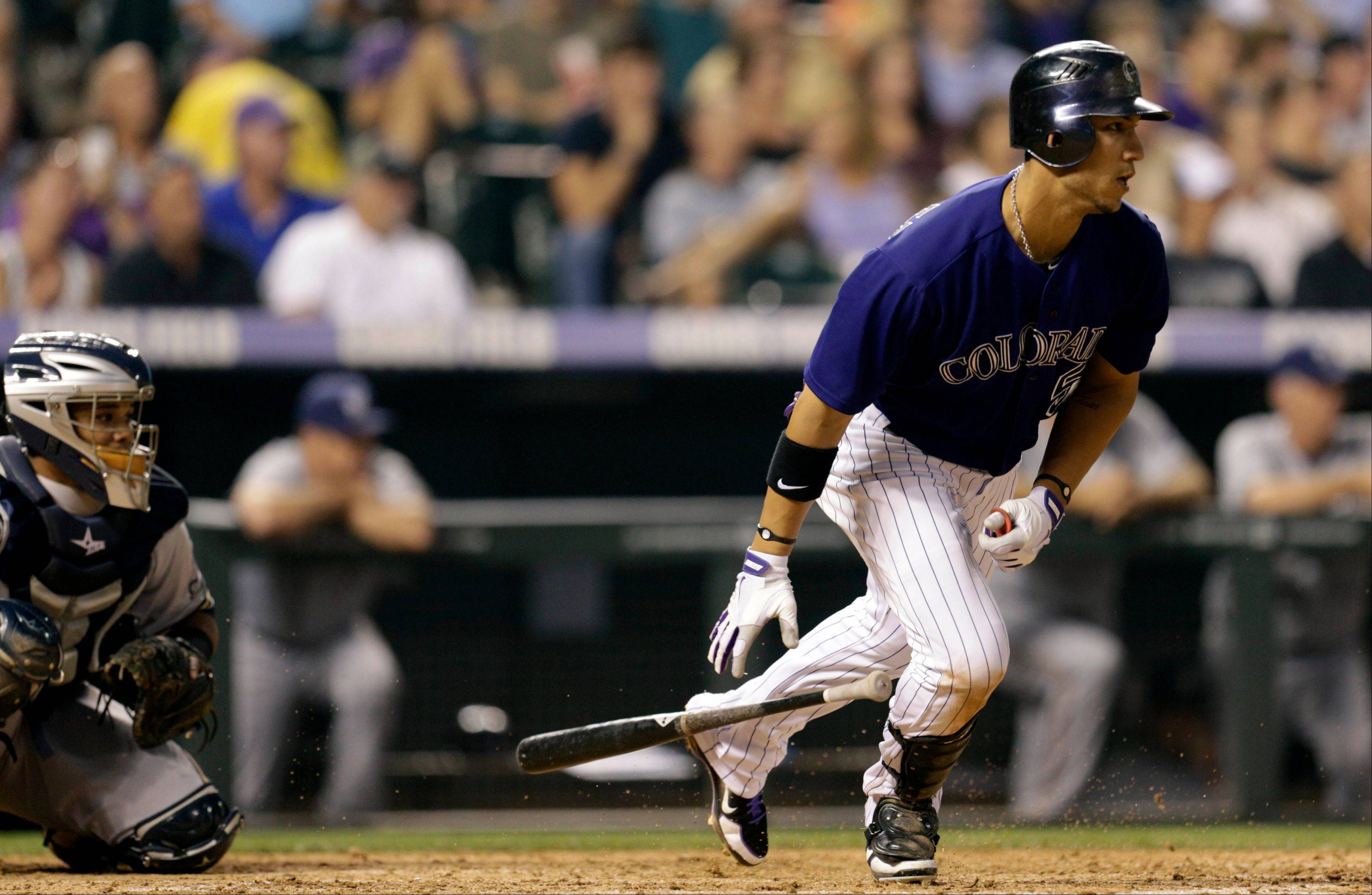 Colorado Rockies outfielder Carlos Gonzalez, right, hits a single against the Milwaukee Brewers Tuesday during the fifth inning. Brewers catcher Martin Maldonado watches the play.