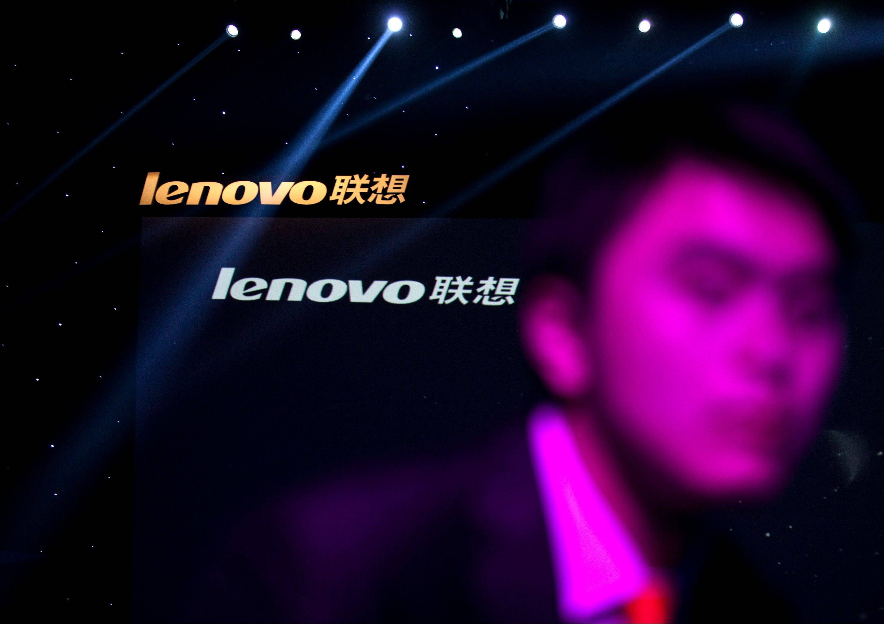 A Lenovo employee, front, walks near the company logos during a Lenovo promotional event in Beijing, China.