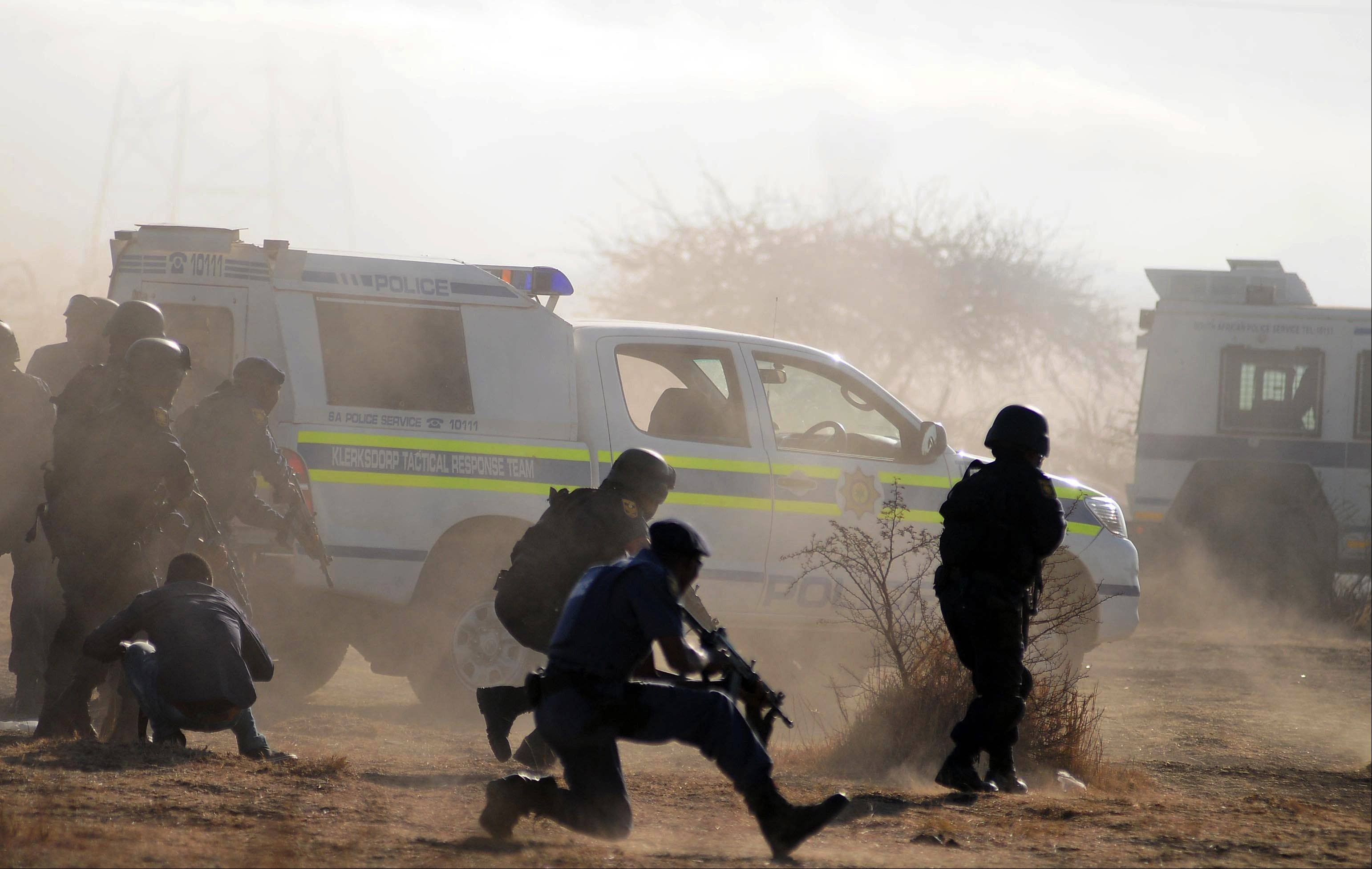 Policemen surrounded by teargas and dust open fire Thursday on striking miners at the Lonmin Platinum Mine near Rustenburg, South Africa.
