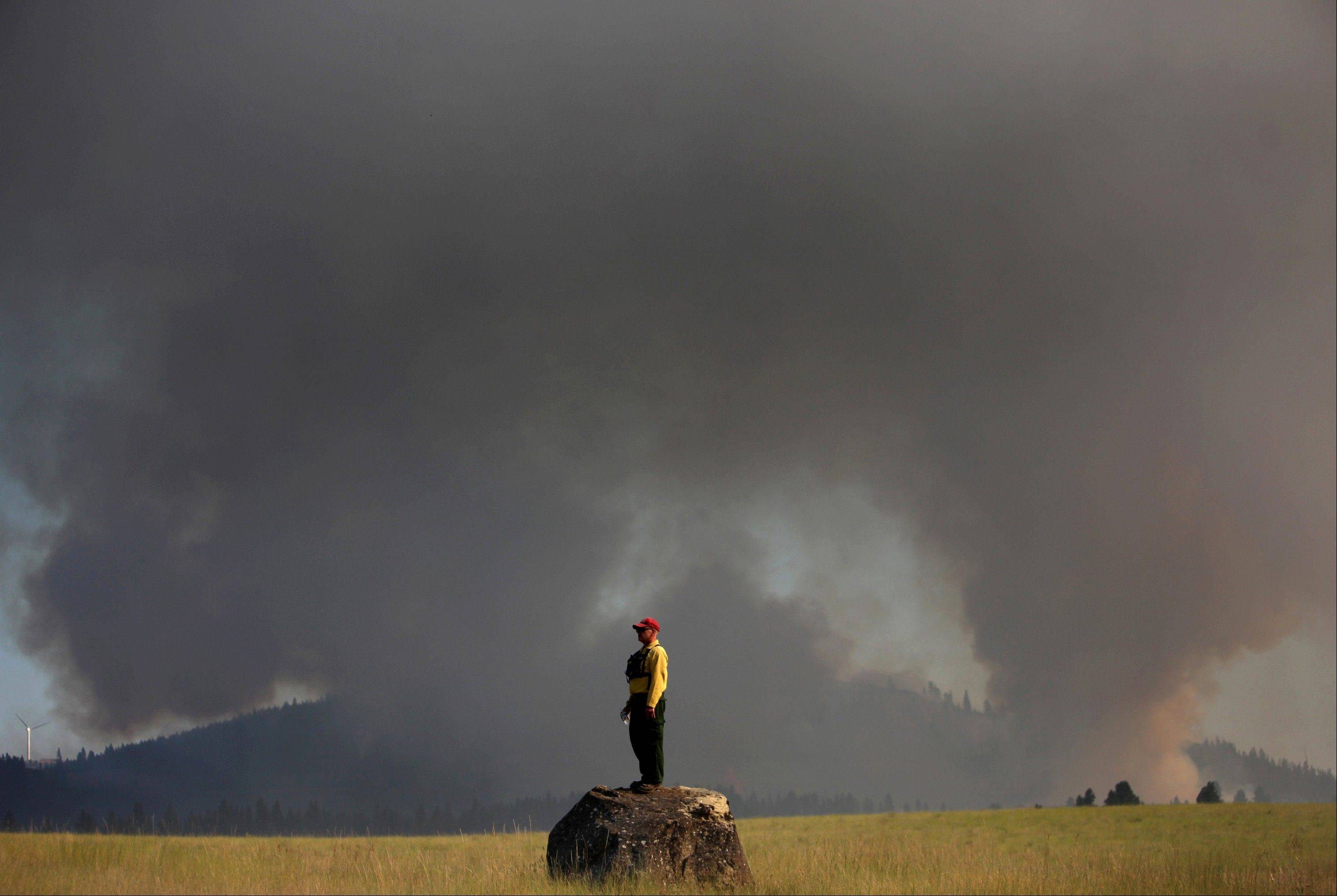 Marcus Johns with the Department of Natural Resources, watches as the Taylor Bridge Fire burns on the south side of Highway 970 near Swauk Prairie Road on Wednesday, Aug. 15, 2012 near Cle Elum, Wash. The Taylor Bridge Fire has forced hundreds to evacuate and has burned dozens of homes.