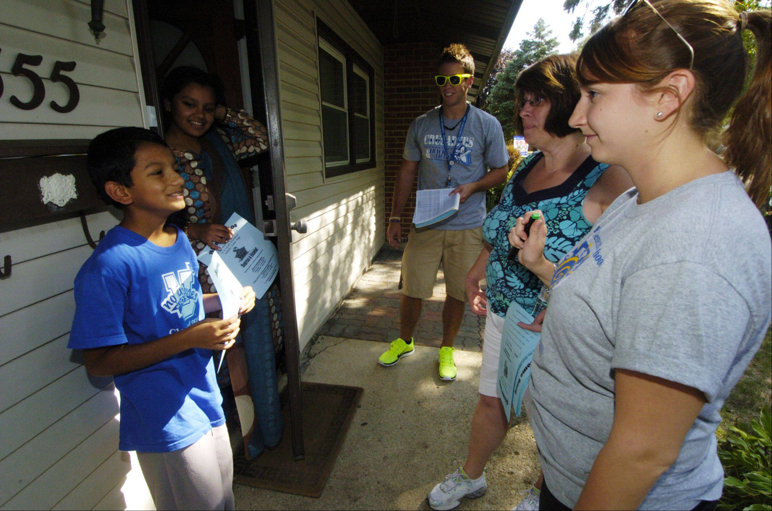 Fourth-grade teacher Nancy Hellstrom, second from right, and literacy coach Melissa Howard, right, talk to Syed Rahman on Wednesday as teachers and staff from Anne Fox Elementary School in Hanover Park visit the homes of students to welcome them back to school.