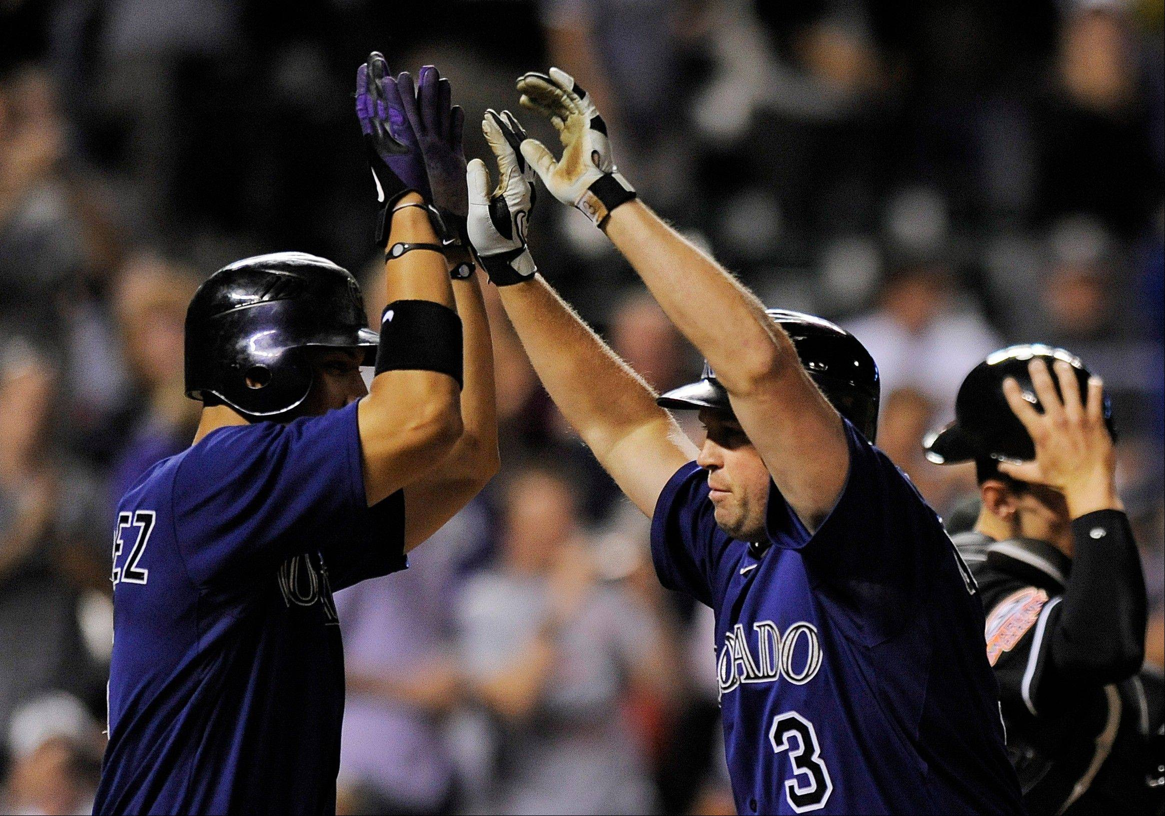 The Rockies' Carlos Gonzalez, left, congratulates Michael Cuddyer on his two-run home run in the sixth inning Thursday against the Marlins in Denver.