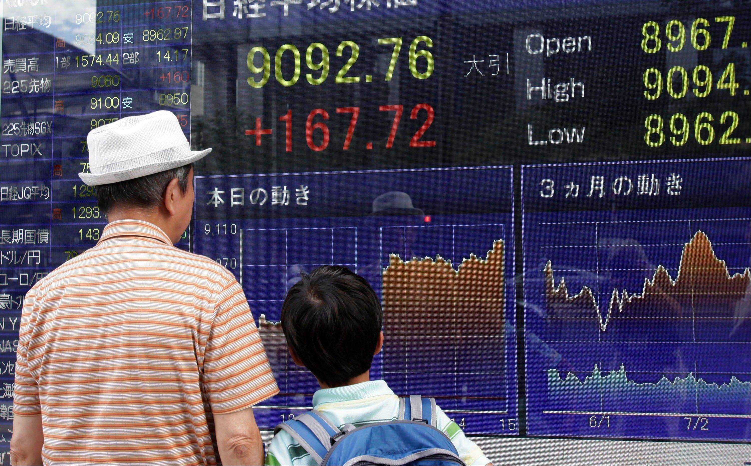 A man and a child look at a securities firm's electronic stock board in Tokyo Thursday.