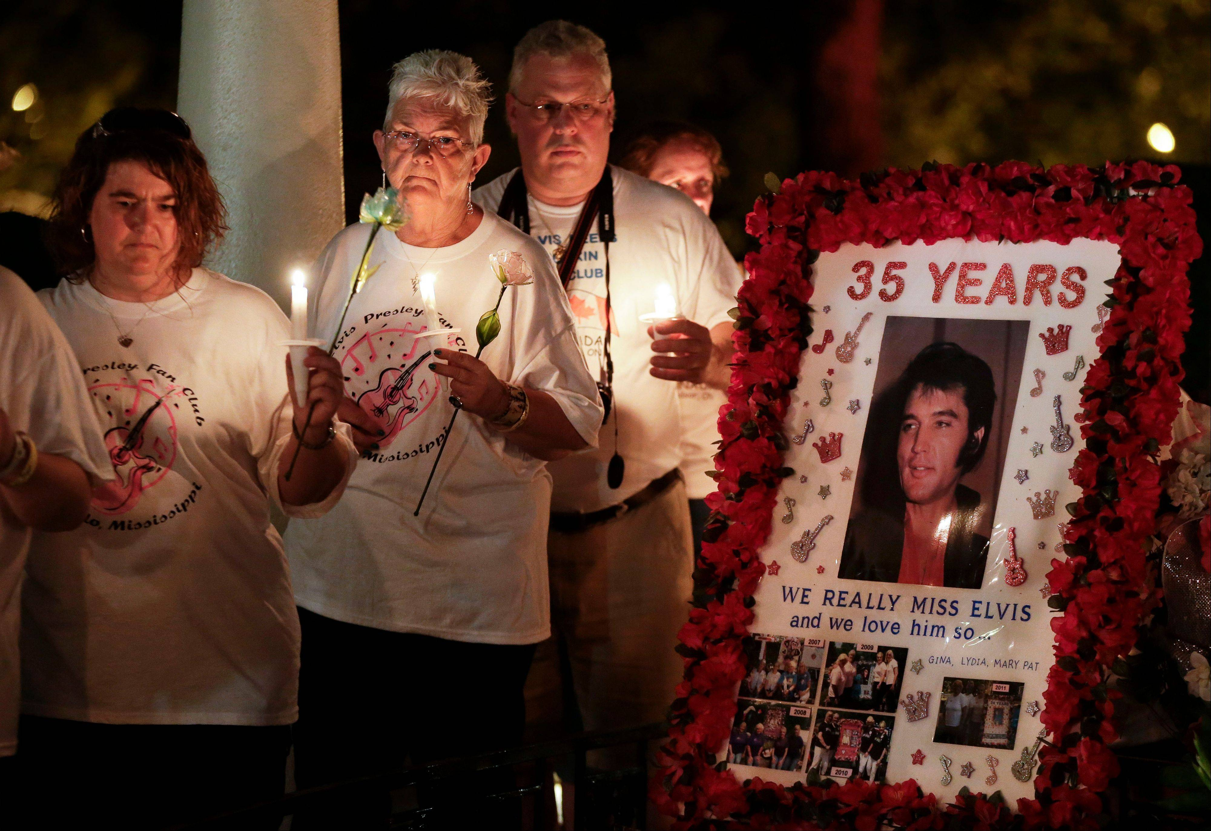 Elvis Presley fans walk past his grave during a candlelight vigil at Presley's Memphis home on Wednesday.