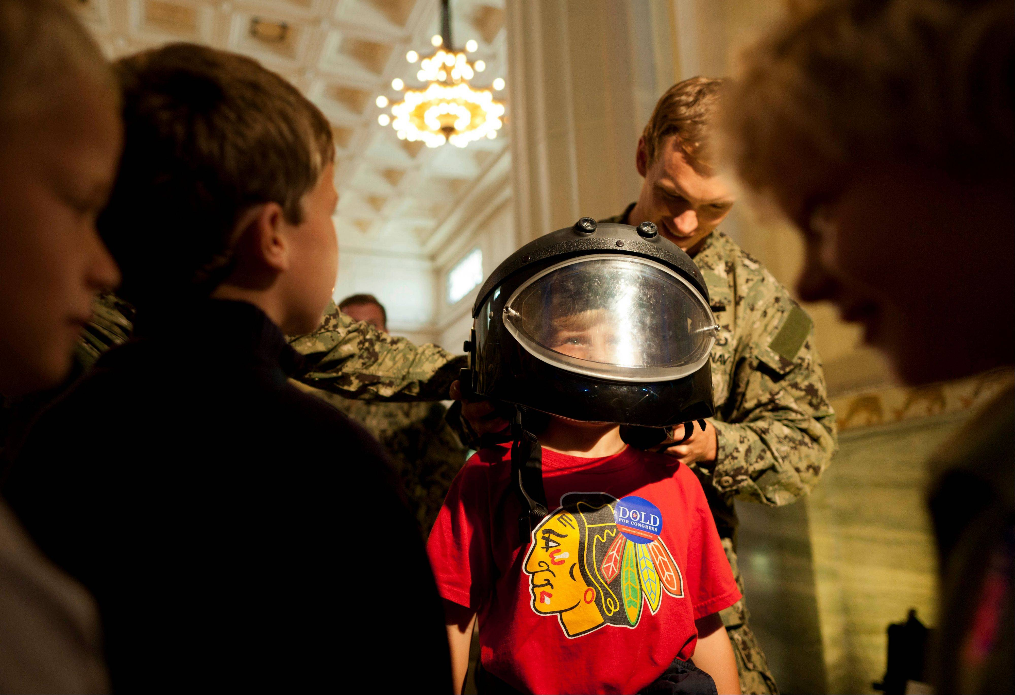 A member of the Navy Explosive Ordnance Disposal Mobile Unit Two helps boys try on protective equipment during Navy Week on Thursday at Chicago's Shedd Aquarium.
