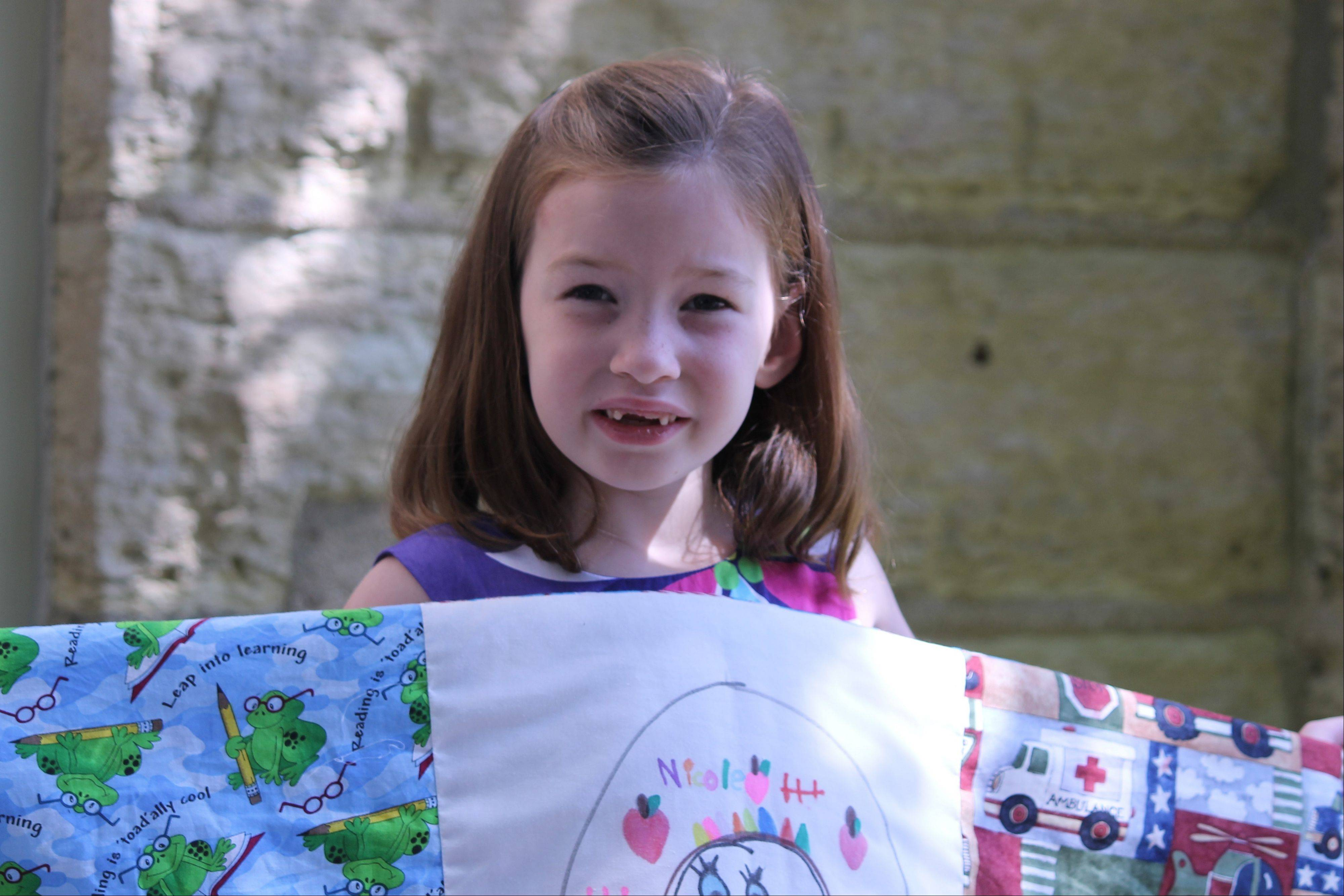 Nicole Magerkurth, 5, displays her first quilt. Inspired by Batavia's Quilt and Textile Show, Nicole plans to enter a quilt in next year's show.