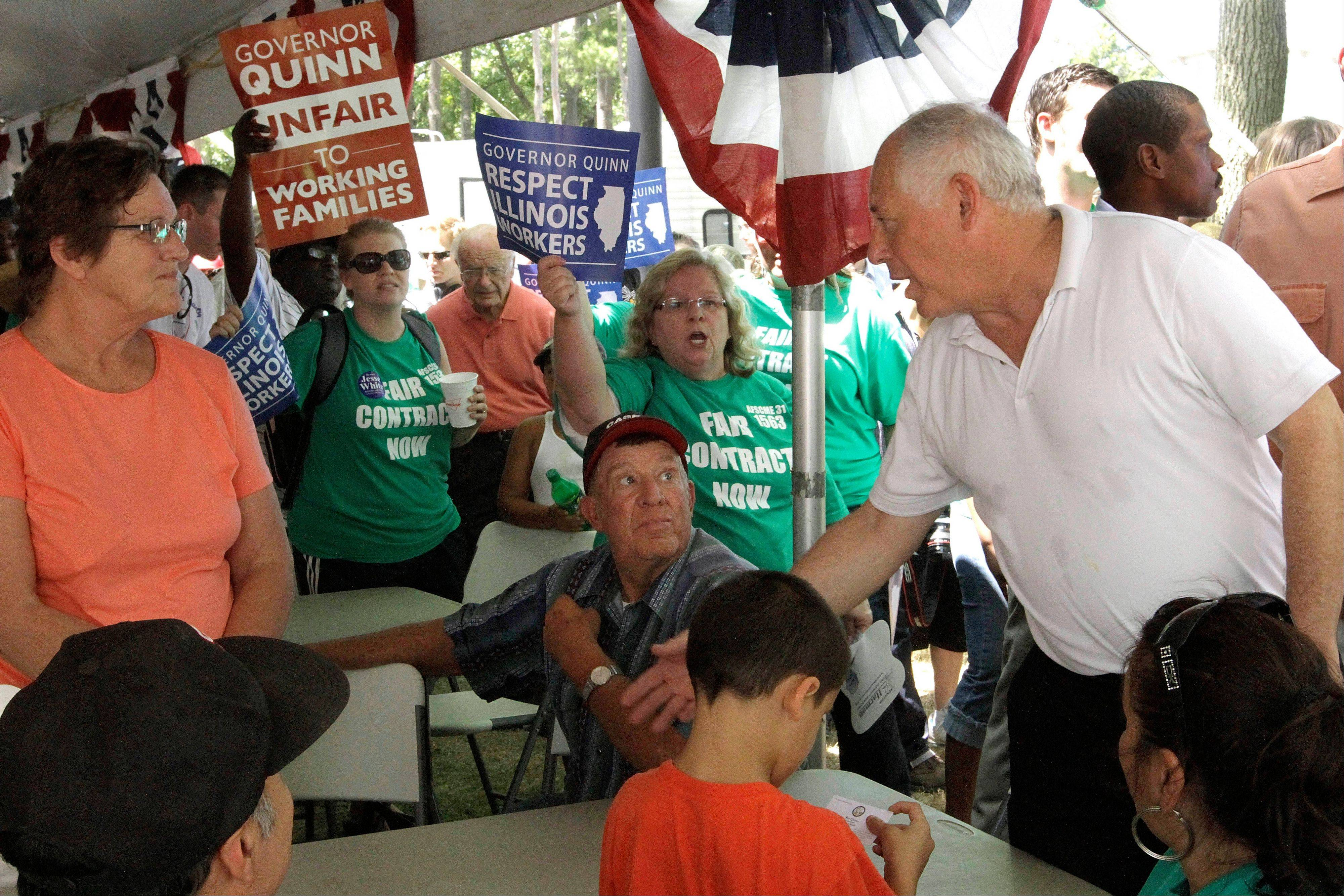 Surrounded by booing union members, supporters and labor leaders, Gov. Pat Quinn, right, still tries to greet those attending the Governor's Day rally at the Illinois State Fair yesterday.