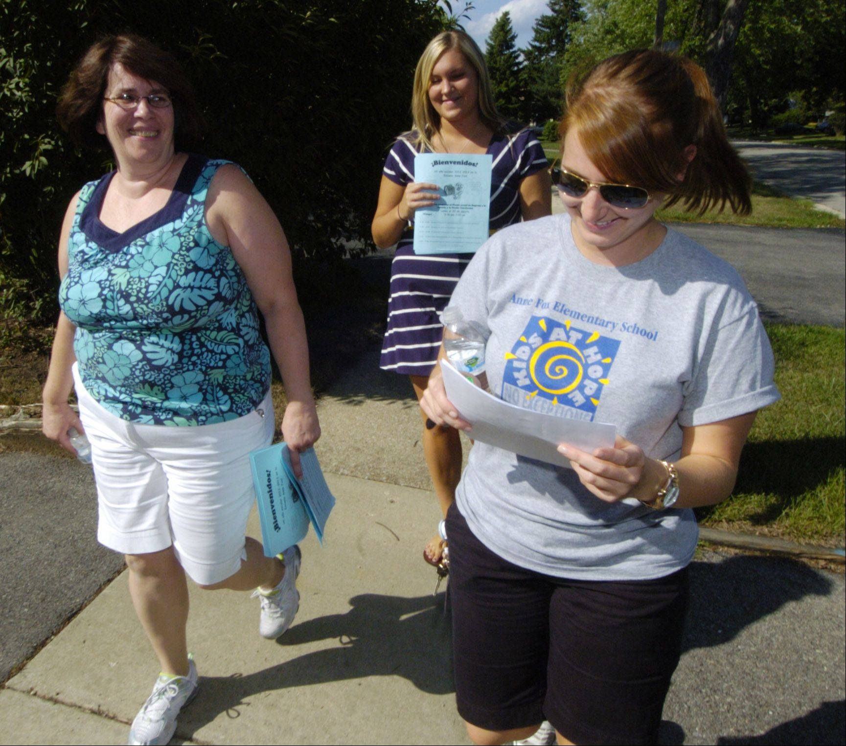 From left, Nancy Hellstrom, Katie Shirmulis and Melissa Howard look to see which house they are going to next.
