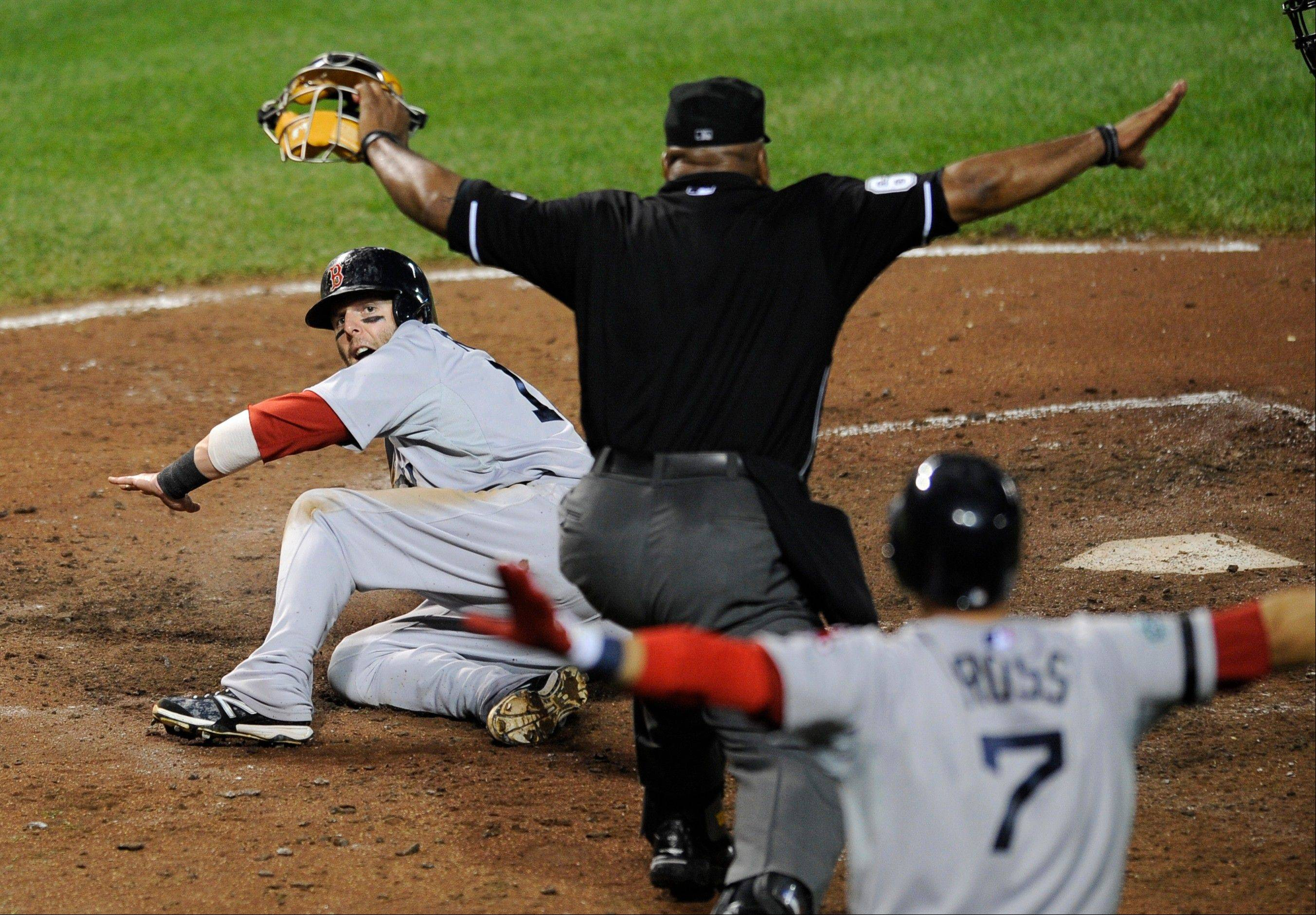 "Boston's Dustin Pedroia looks up as home plate umpire Laz Diaz and teammate Cody Ross signal ""safe"" when he scores on a sacrifice fly by Adrian Gonzalez Thursday in Baltimore."