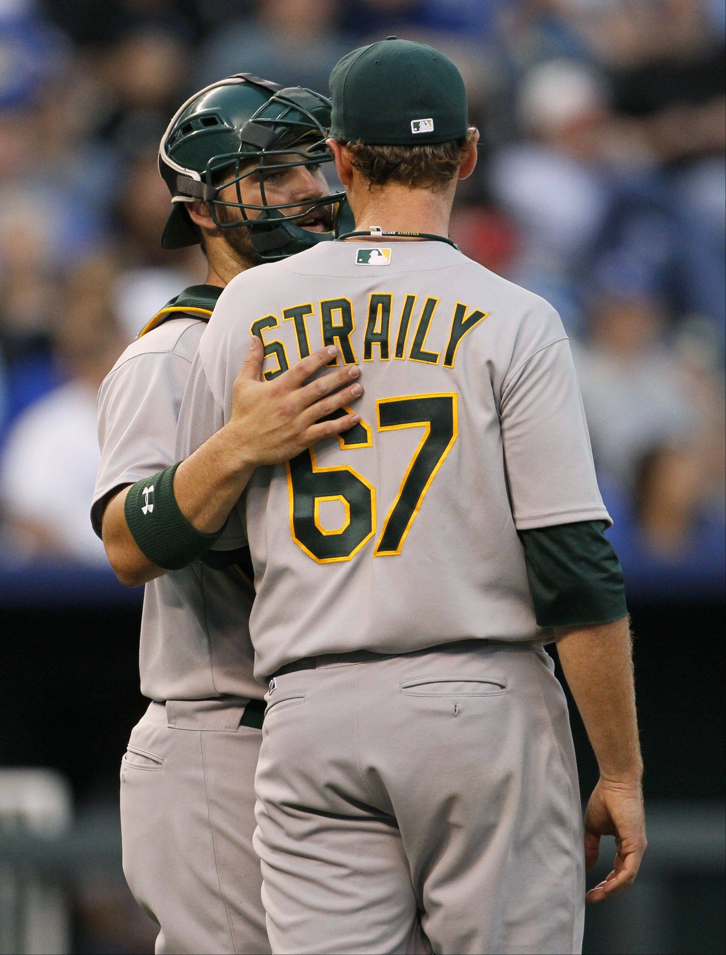 Oakland Athletics catcher Derek Norris, left, talks with pitcher Dan Straily after the rookie loaded the bases in the second inning Thursday in Kansas City.