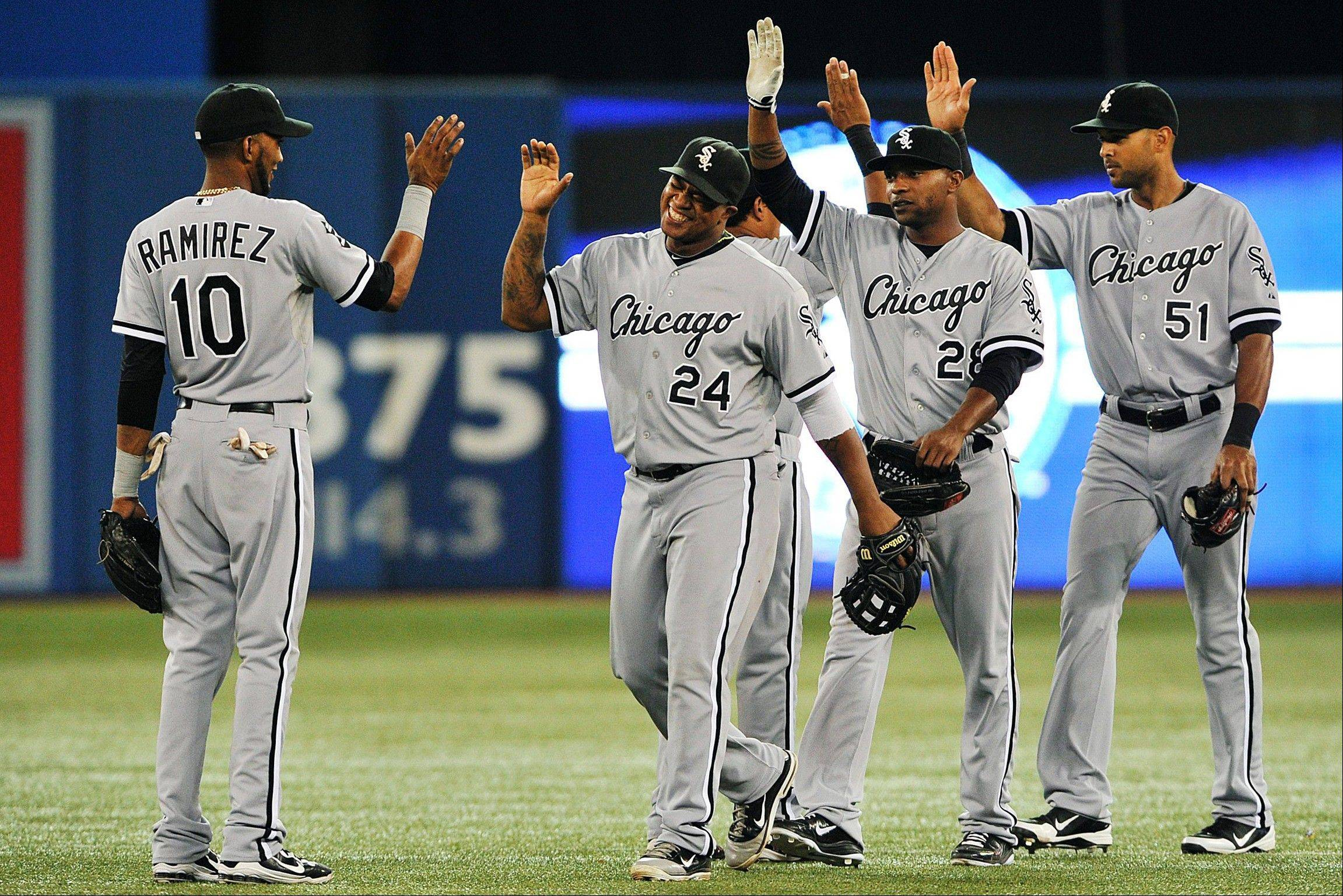 The White Sox' Dayan Viciedo (24) smiles as he celebrates with Alexei Ramirez (10), Dewayne Wise (28) and Alex Rios (51) following a 7-2 win over the Toronto Blue Jays. Barring an apocalyptic collapse down the stretch, the White Sox are going to the playoffs for the first time since 2008.