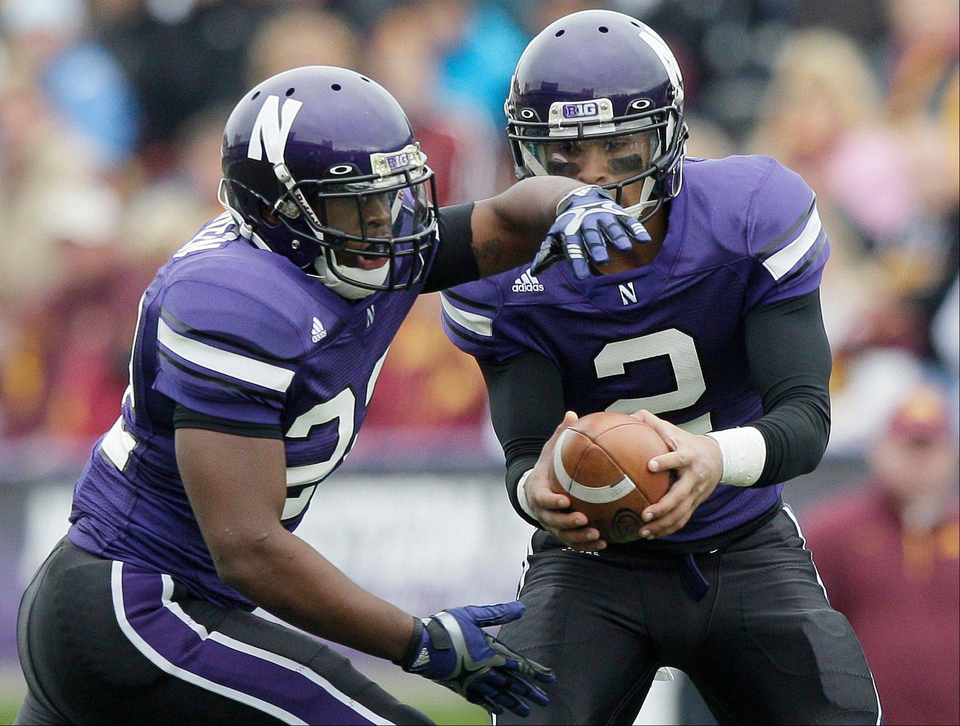 Northwestern quarterback Kain Colter hands the ball off to running back Treyvon Green (22) during a game against Minnesota in Evanston.