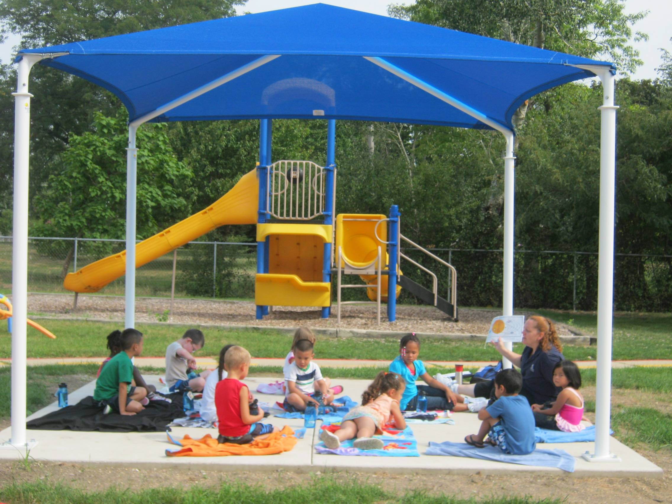 Preschool students at the Glen Ellyn KinderCare Learning Center listen to their teacher during story time under their new playground shade structure.