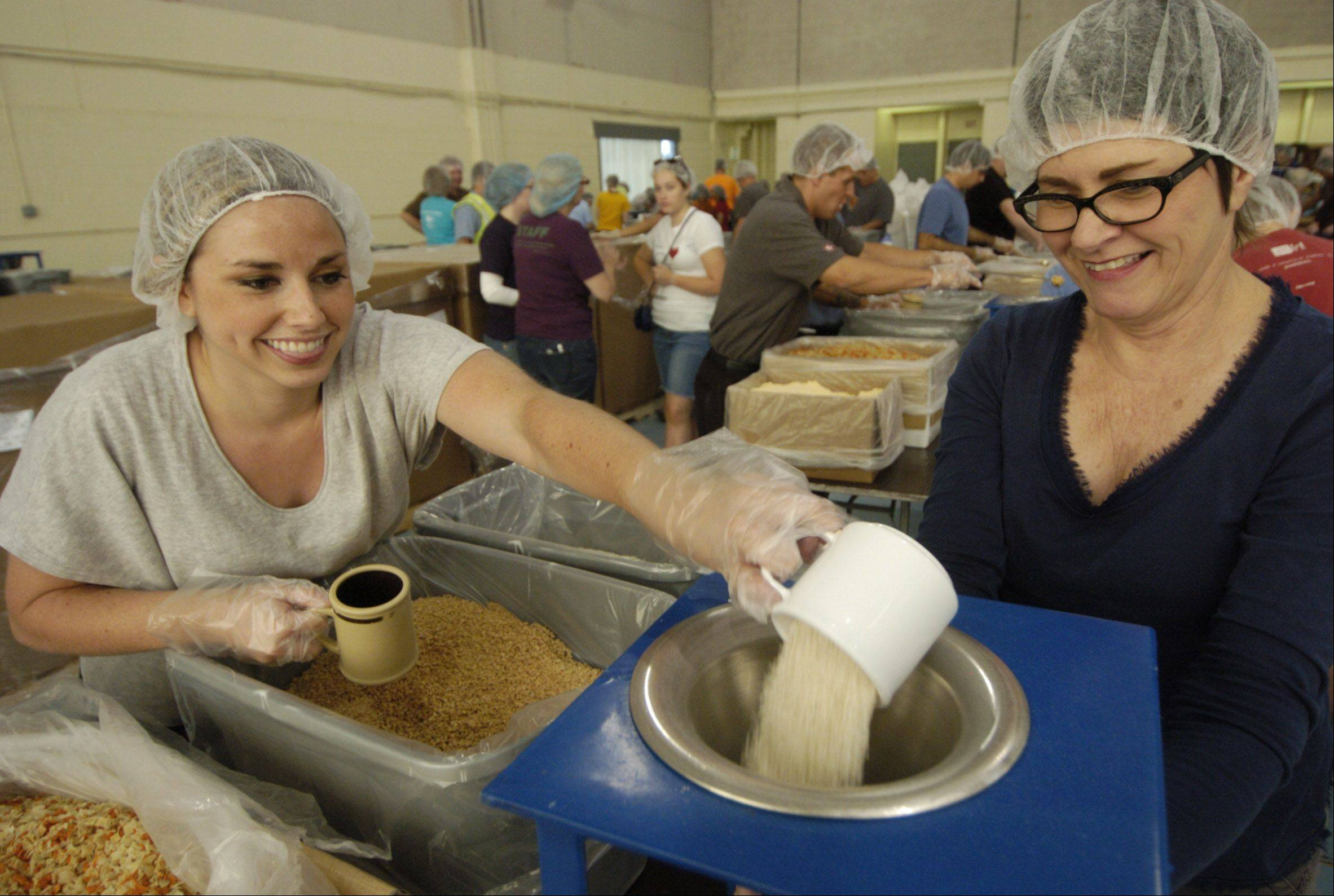 Kristin Horsey, left, of Astraeus Advisers in Park Ridge and Kathleen Joleaud of Magnetar Capital in Evanston help assemble meals Friday at Priester Aviation in Wheeling