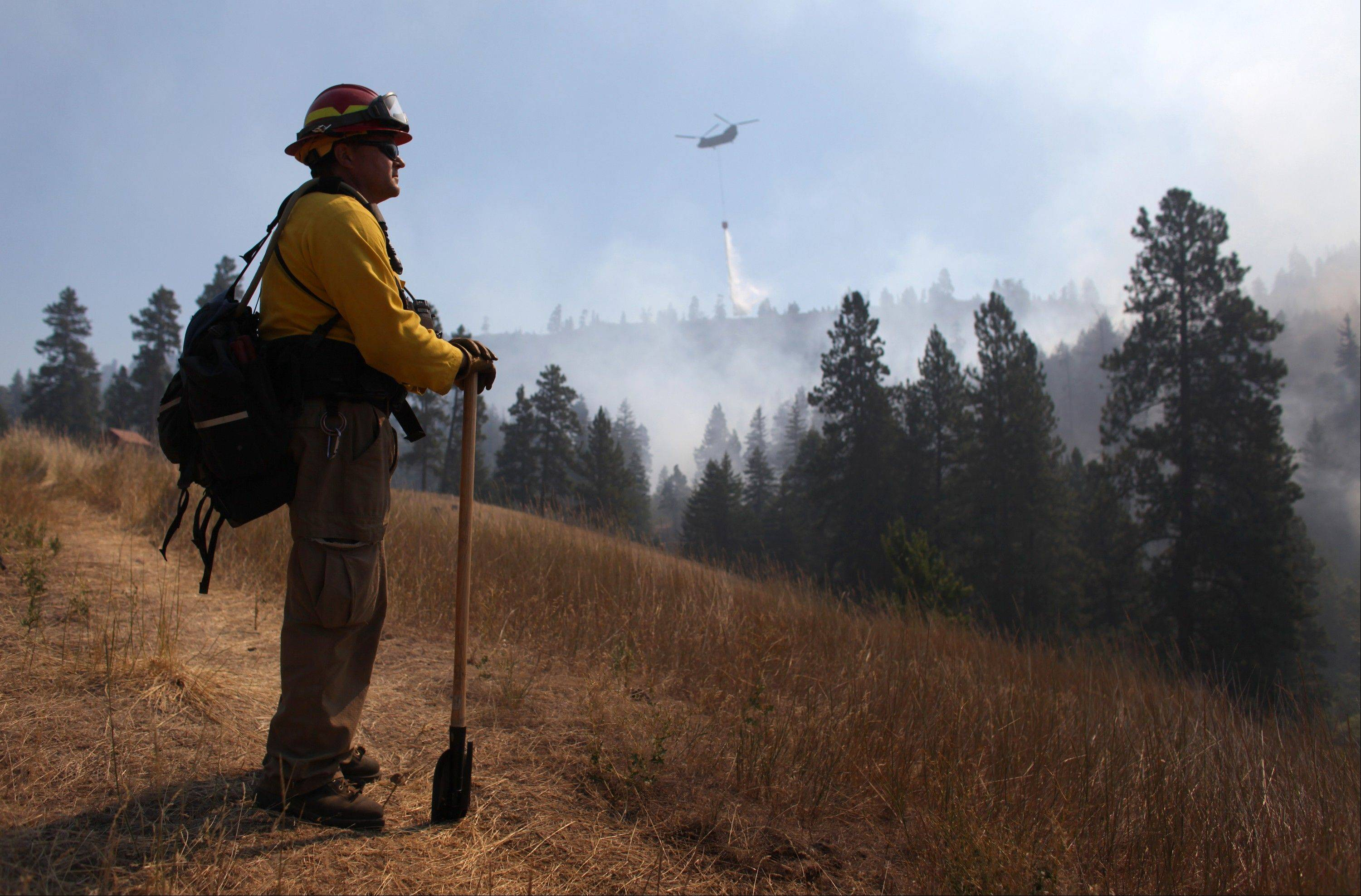 Tracy Summers of Toledo, Wash. monitors the scene above Hidden Valley Ranch where fire crews worked to halt progression of the Taylor Bridge Fire on Thursday, August 16, 2012 near Cle Elum, Wash. The Taylor Bridge Fire has forced hundreds to evacuate and has burned dozens of homes near Cle Elum, Wash.