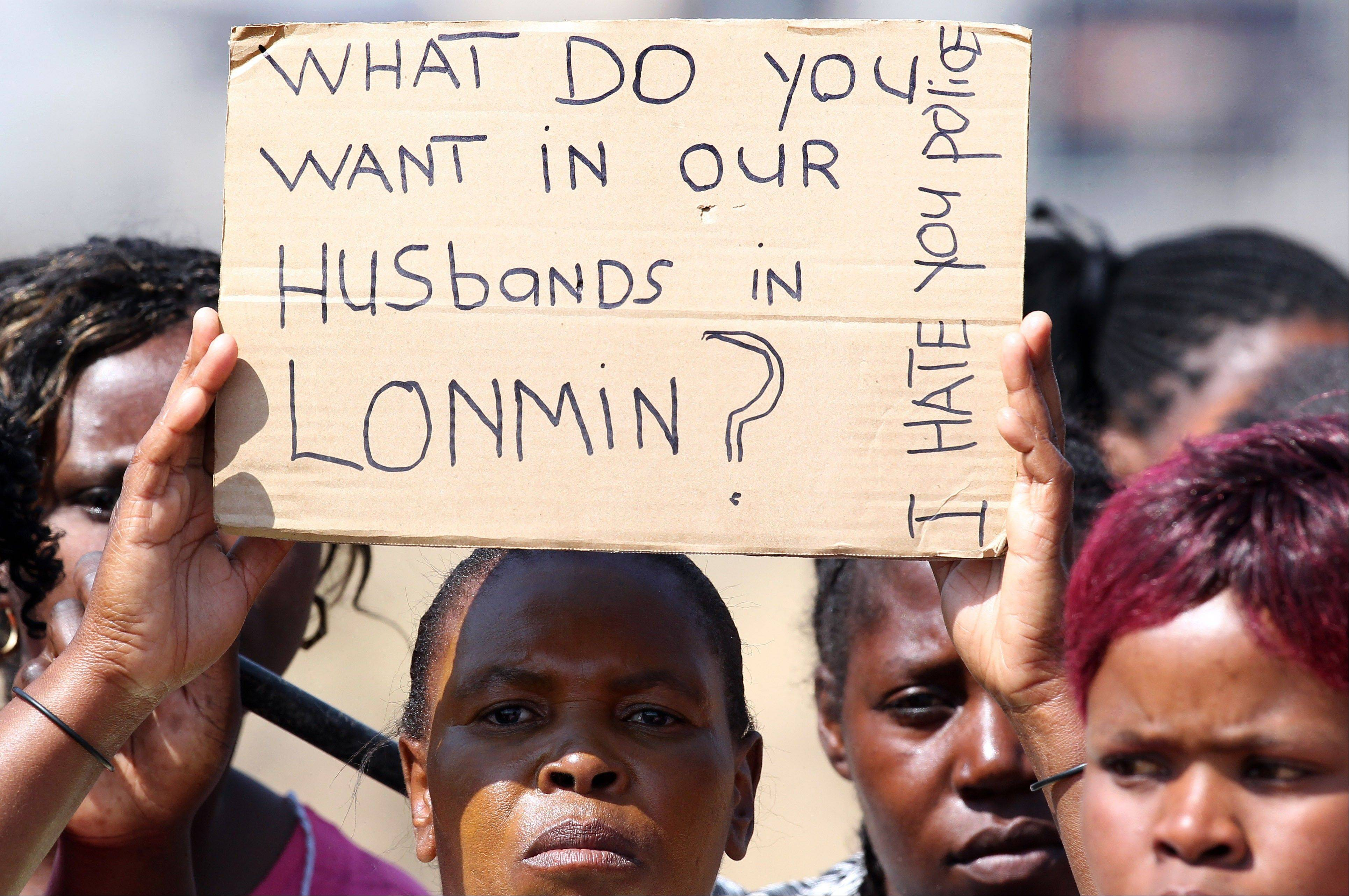 A woman holds a placard as she protests against the police shooting of miners Thursday at the Lonmin mine near Rustenburg, South Africa, Friday, Aug. 17, 2012. Police chief Mangwashi Victoria Phiyega says 34 miners died and another 78 were wounded when police opened fire on strikers in one of the worst police shootings in South Africa since apartheid.