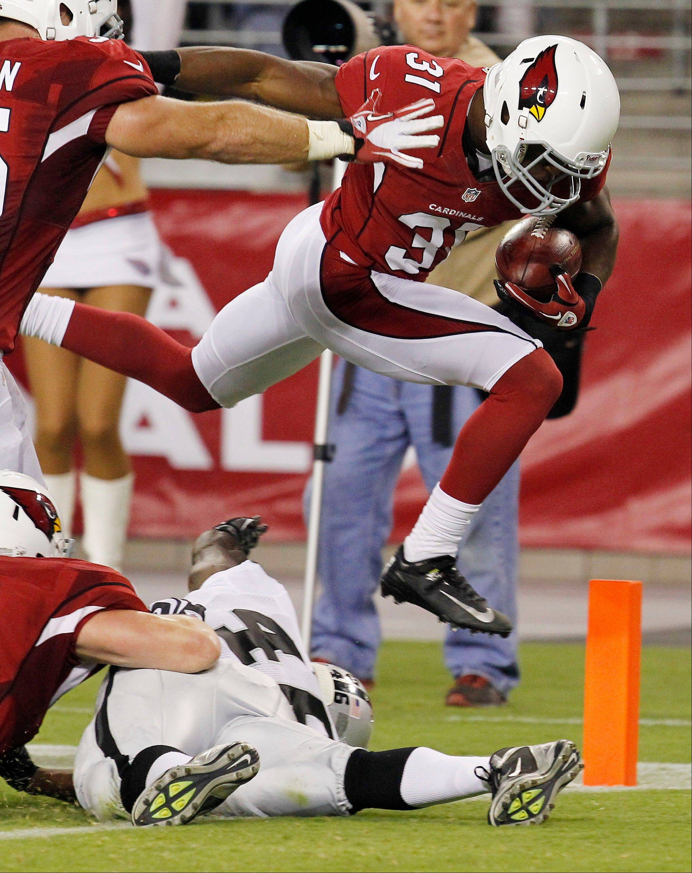 The Cardinals' Justin Bethel leaps over Oakland's Lonyae Miller and into the end zone for a touchdown after blocking a punt Friday in a preseason game in Glendale, Ariz.