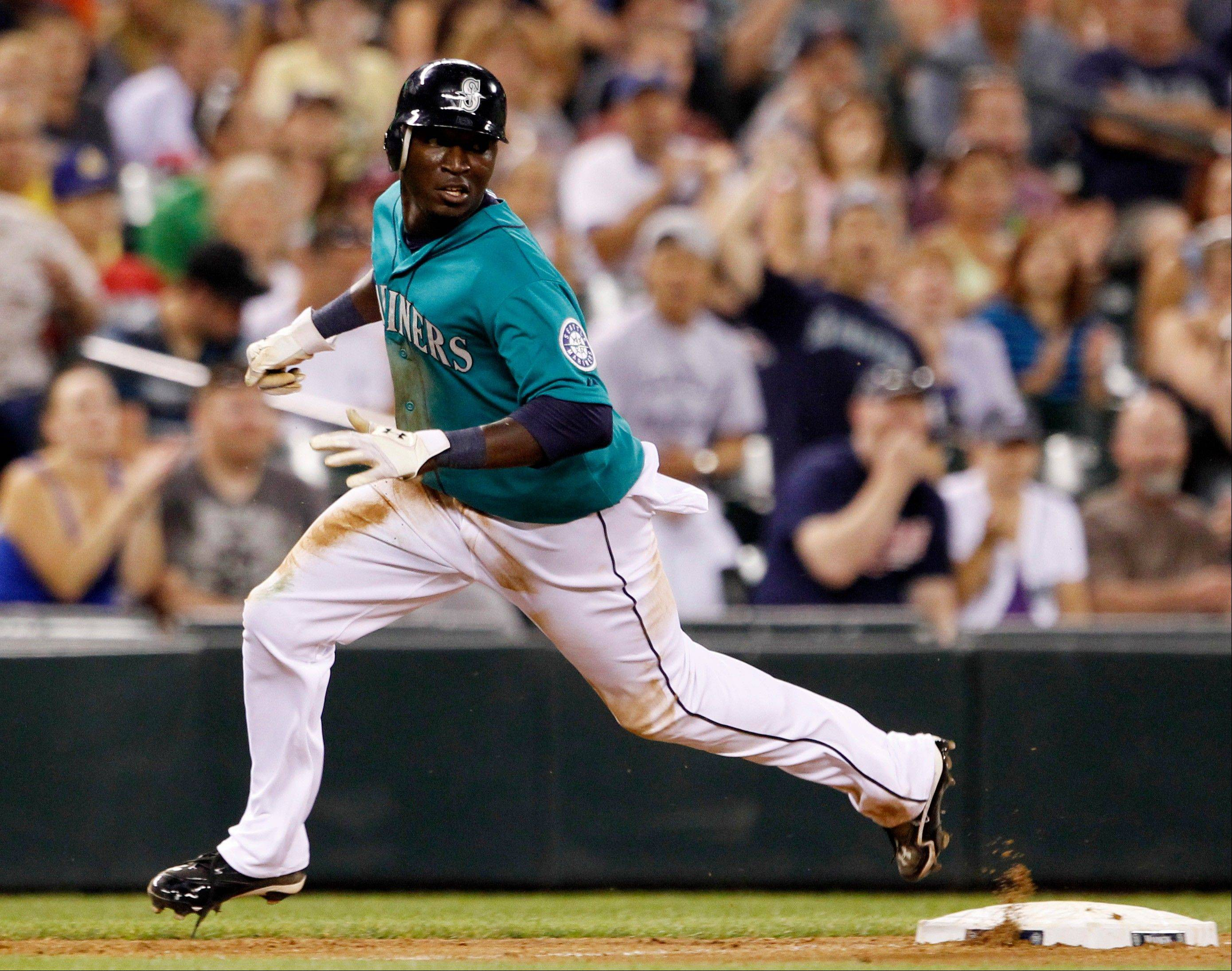 The Mariners' Trayvon Robinson comes around to score against the Minnesota Twins in the sixth inning Friday in Seattle.