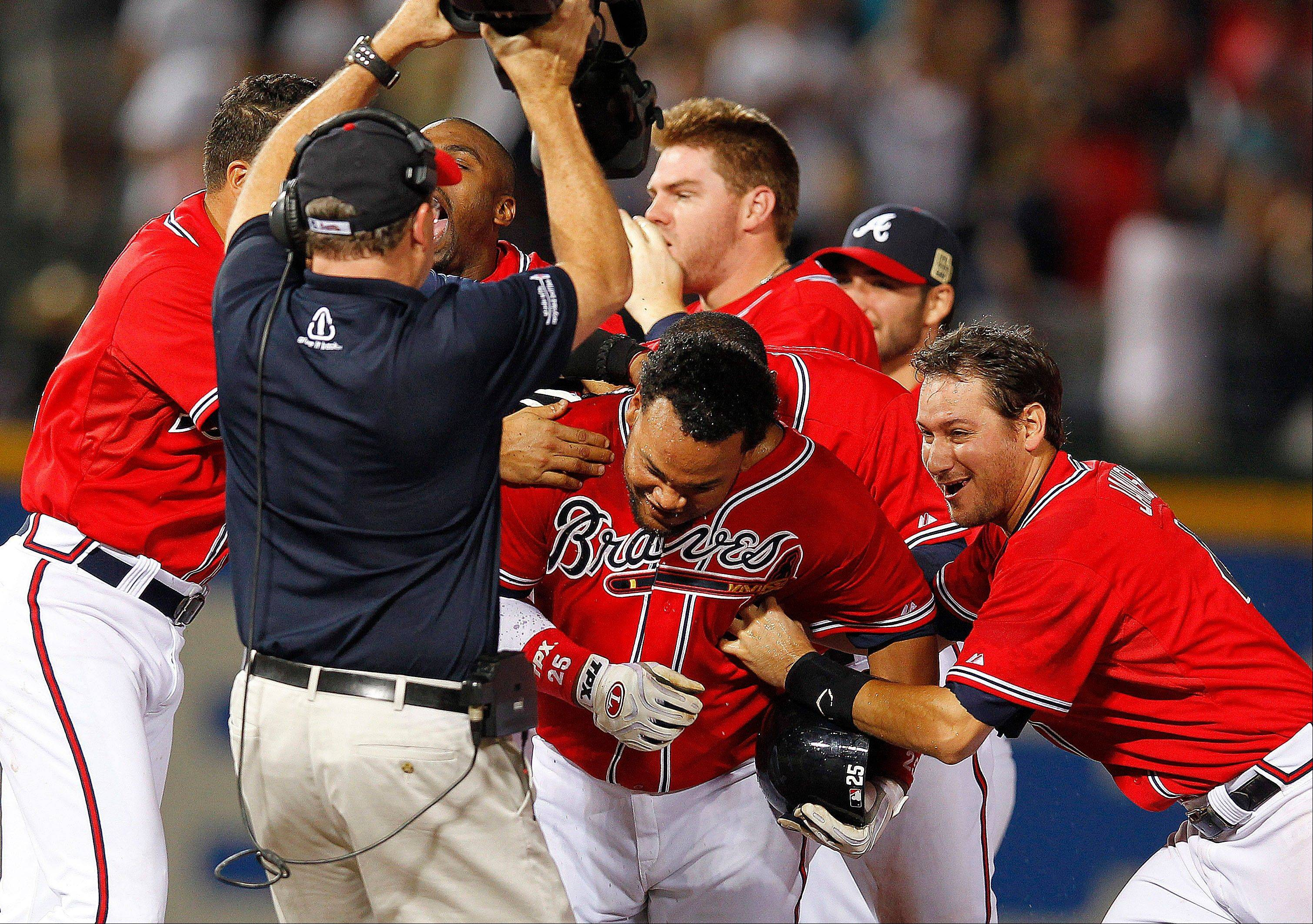 Atlanta pinch hitter Juan Francisco, center, celebrates with teammates after driving in the game-winning run in the 11th inning Friday night at home against the Los Angeles Dodgers.