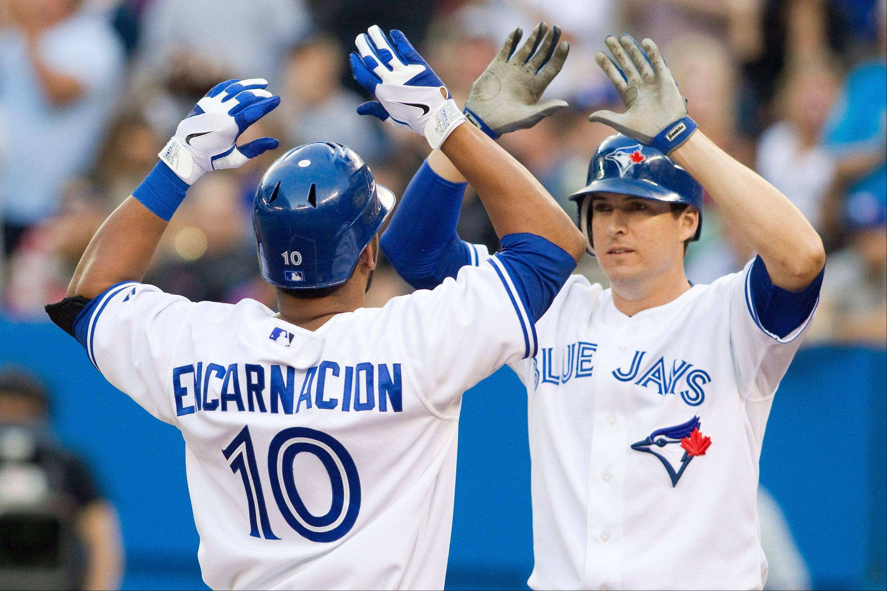 The Blue Jays' Kelly Johnson, right, congratulates teammate Edwin Encarnacion for hitting a two-run home run off Texas Rangers starting pitcher Yu Darvish on Friday in Toronto.