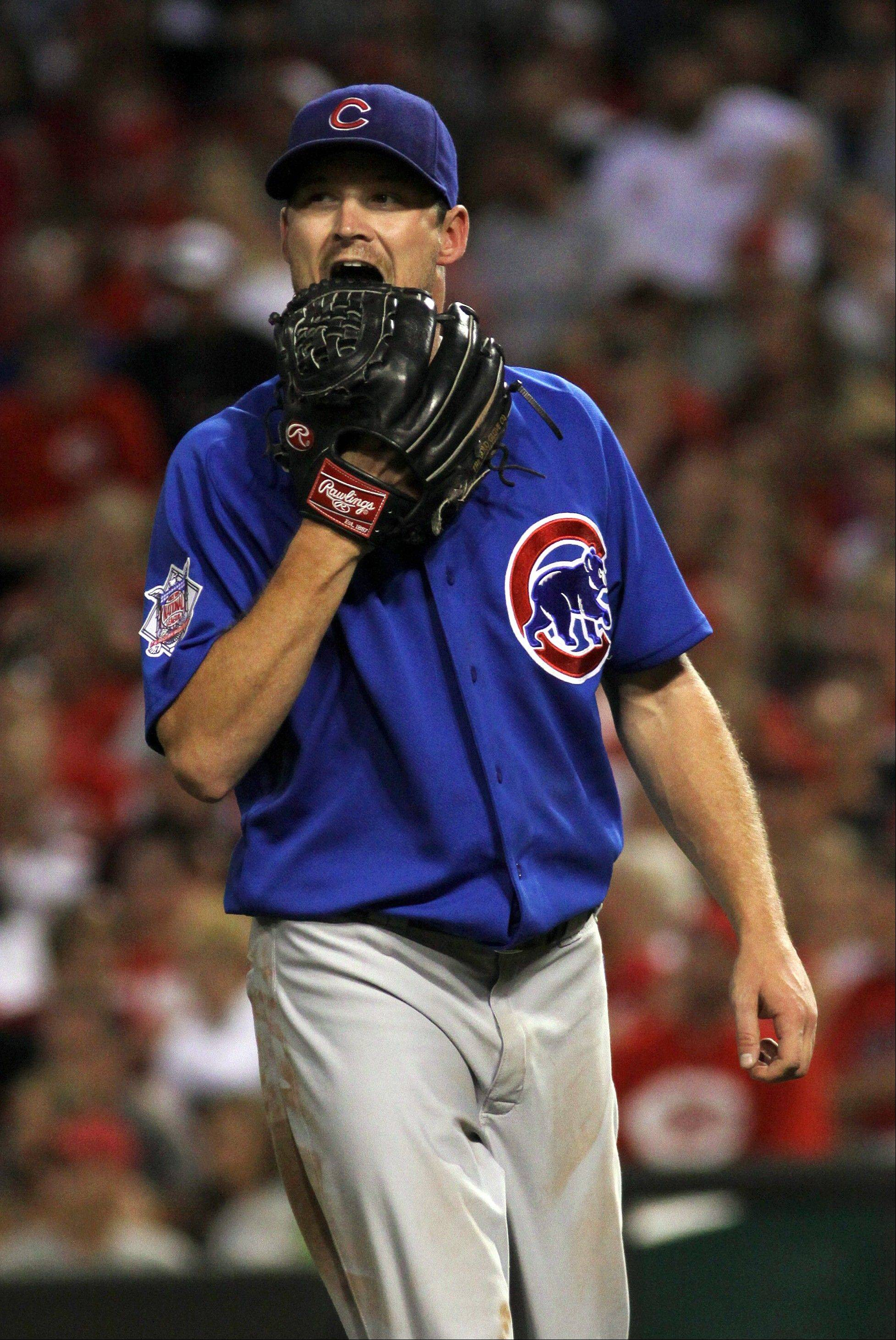 Cubs starter Travis Wood bites his glove as he walks off the field at the end of the fourth inning against the Cincinnati Reds on Friday in Cincinnati.