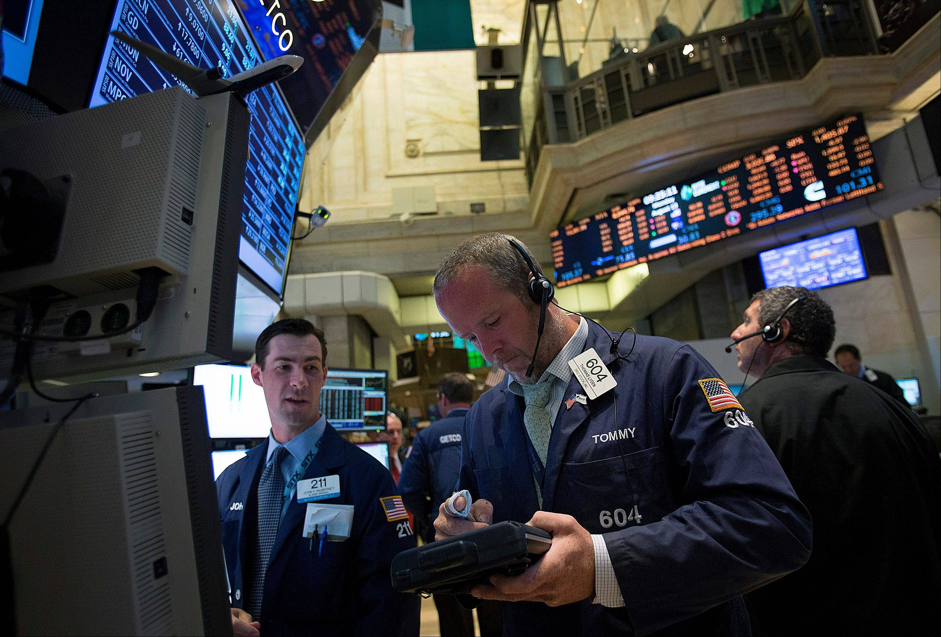 Associated PressTrader Thomas Lyden, center, works on the floor of the New York Stock Exchange on Monday. U.S. stocks fell, with the Standard & Poor�s 500 Index halting its longest rally since 2010.