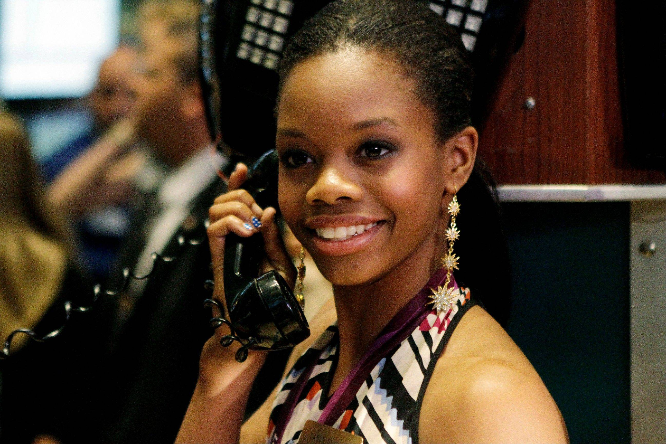 Olympic champion gymnast Gabby Douglas pretends to talk on the phone while posing for photos on the floor of the New York Stock Exchange, Tuesday, Aug. 14, 2012, in New York.