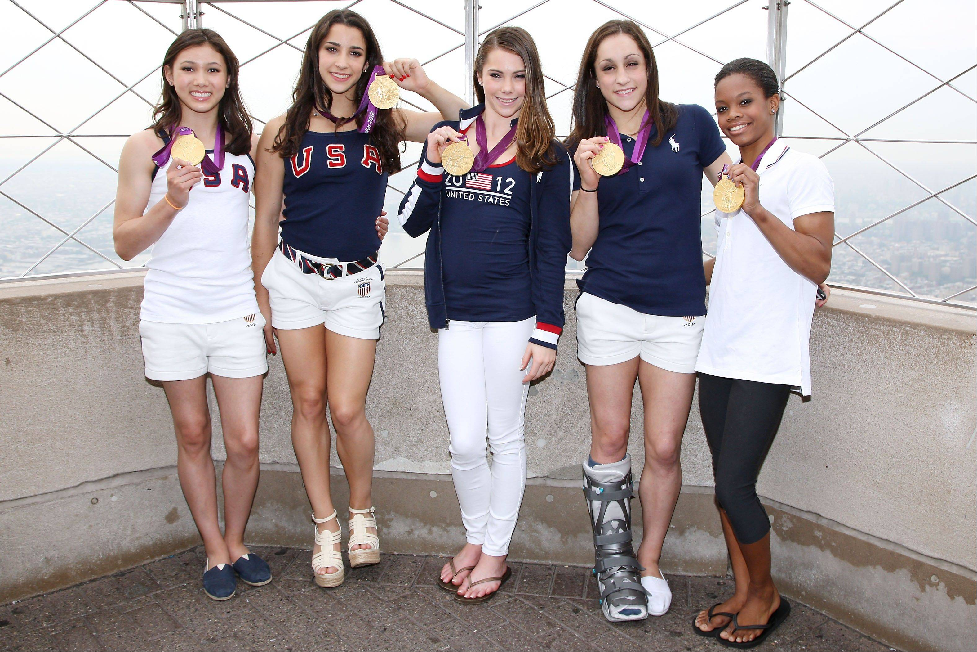 This image released by Starpix shows the gold medal-winning US Women's Gymnastics Team, from left, Kyla Ross, Aly Raisman, McKayla Marone, Jordyn Wieber and Gabby Douglas pose on the observation deck of the Empire State Building, Tuesday, Aug. 14, 2012 in New York.