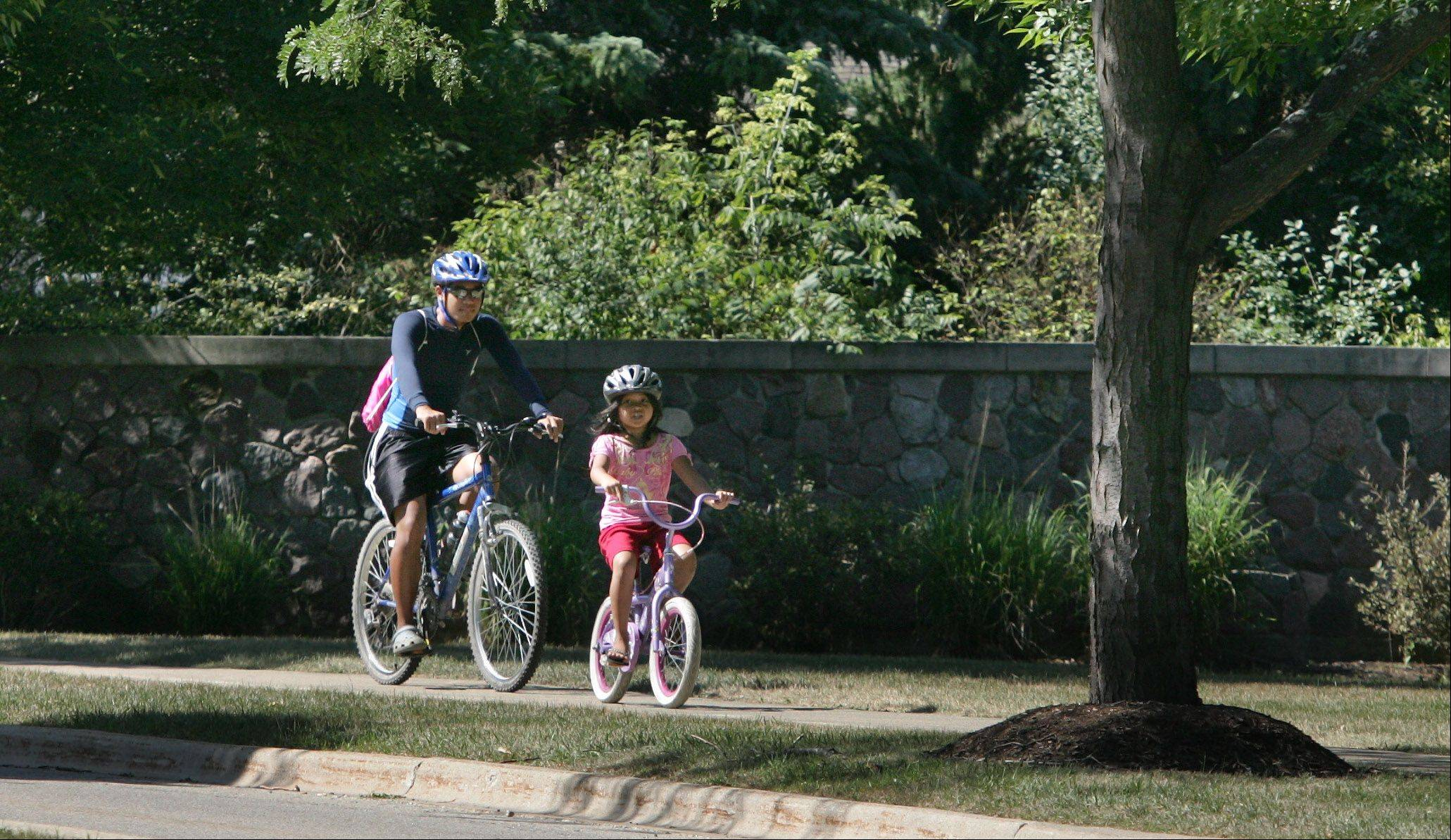 Cousins Justin Ouk and Sarena Yath, both 7, ride their bikes in the Haryan Farms neighborhood in Grayslake.