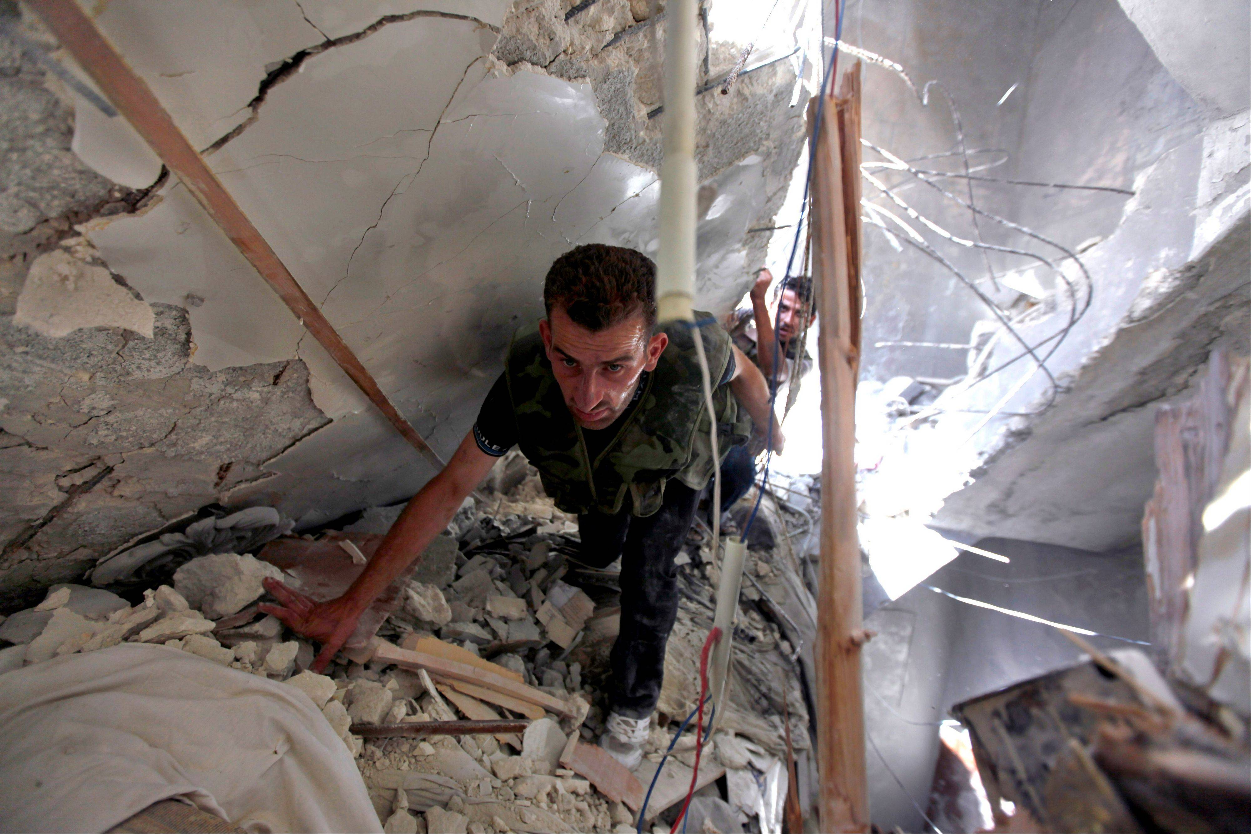 Syrian fighters search for survivors under the rubble of a building destroyed Friday in an airstrike in Aleppo, Syria.