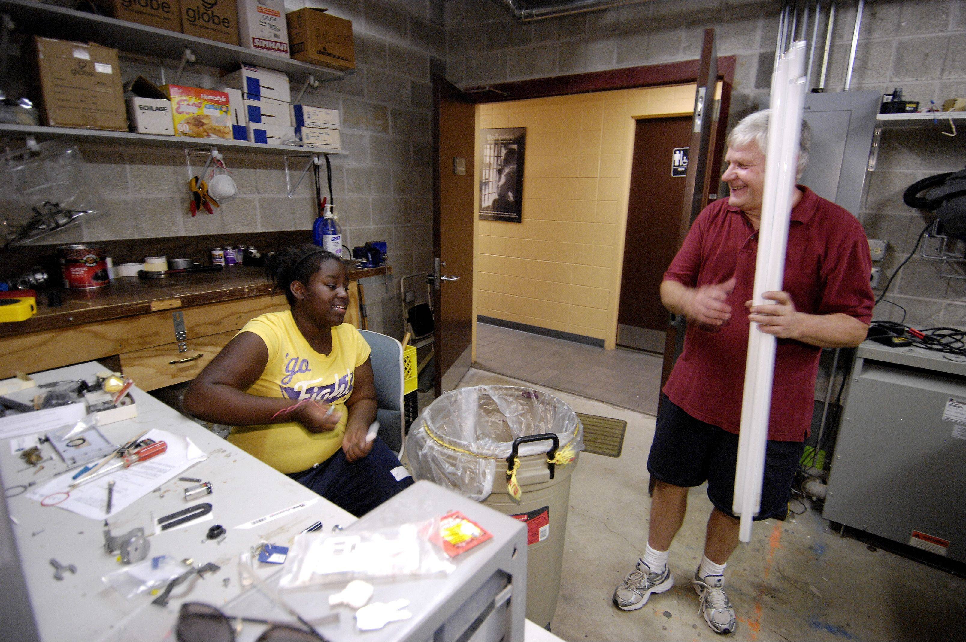 Curt Misavage talks with Nia Williams, 14, while they organize the maintenance room at Outreach Community Ministries in Carol Stream. Misavage is the Facilities Manager and Youth Employment and Education Program mentor at Outreach Community Ministries in Carol Stream.