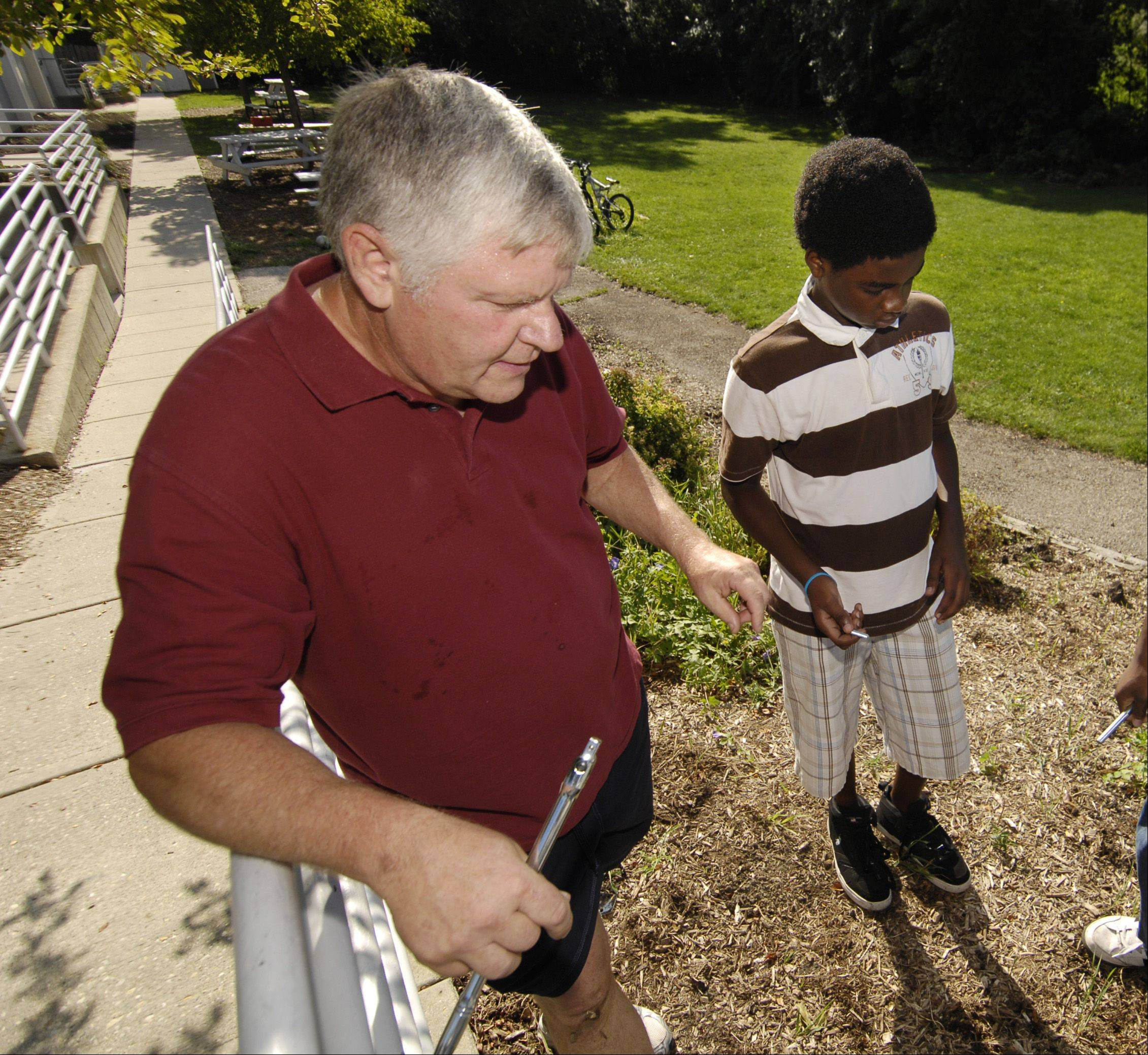 Misavage instructs Mohamed Dafelseed, 13, on fixing a railing.
