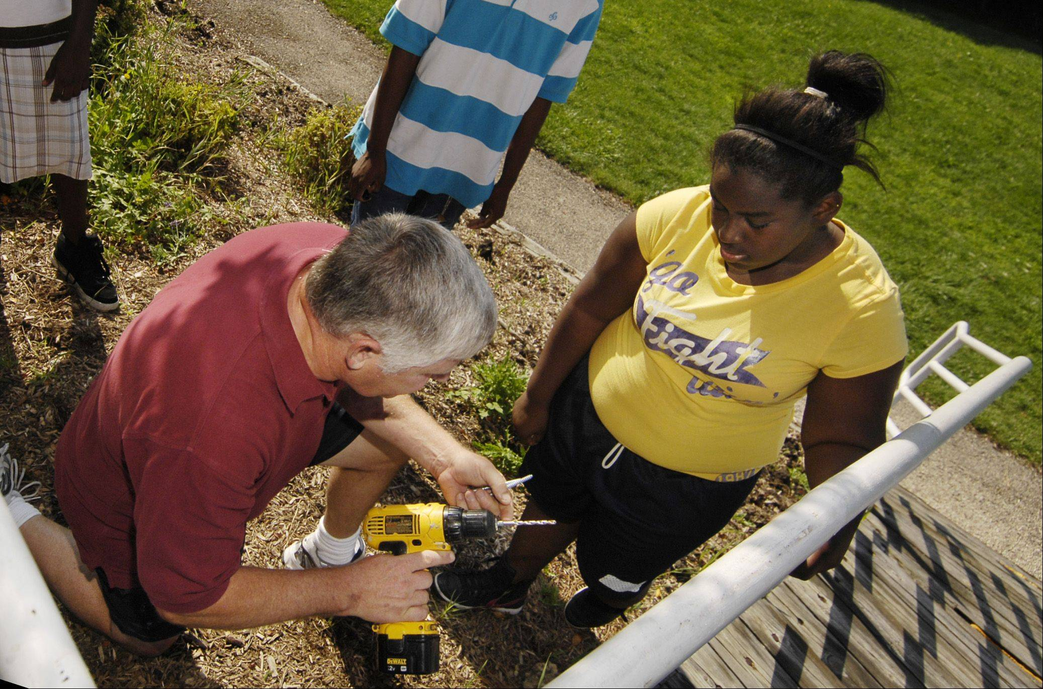 Misavage shows Nia Williams how to use a power drill as he and his team of students repair a railing at Outreach Community Ministries in Carol Stream.