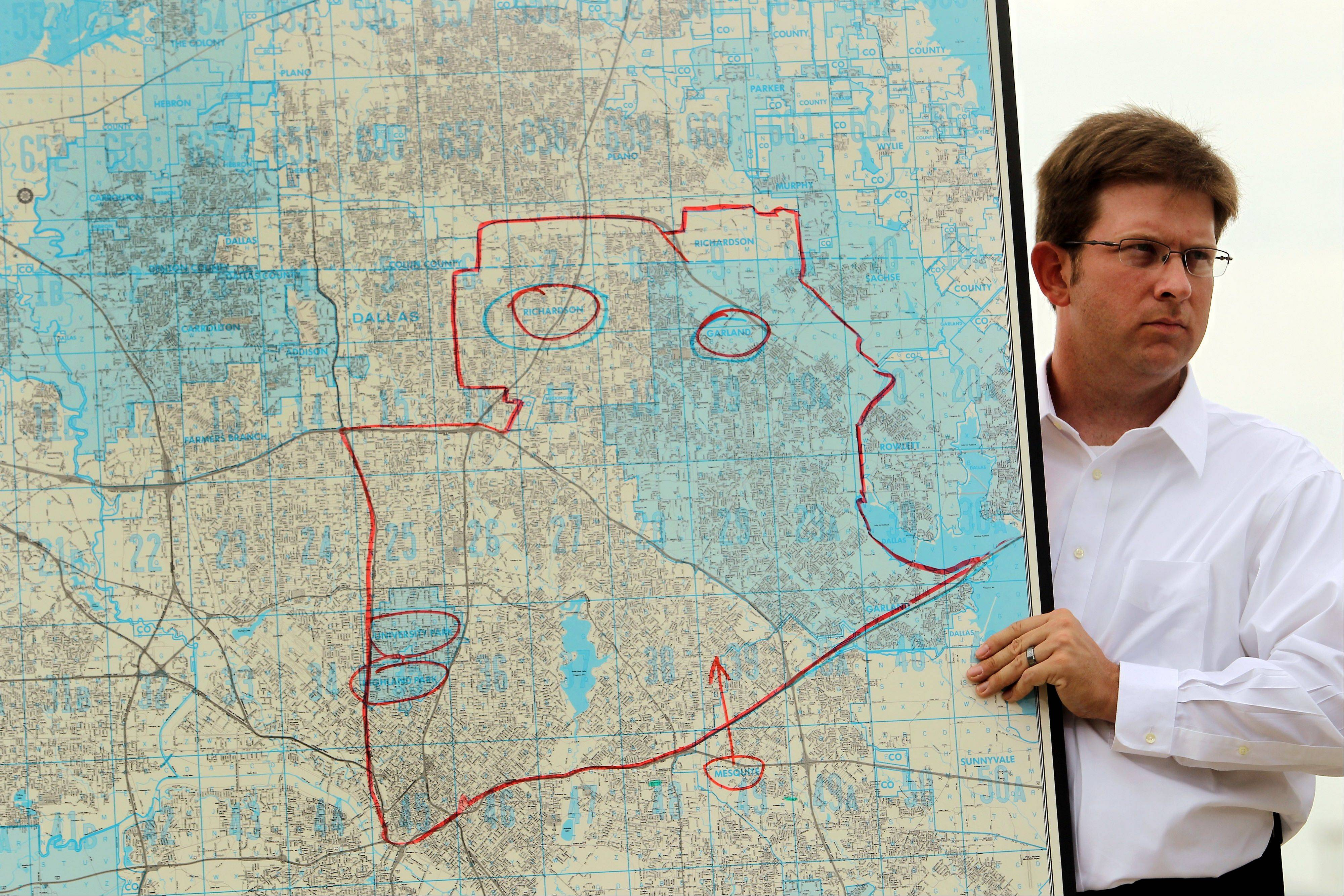 Bryant Sivess, operations manager at Dallas Executive Airport, helps hold up a map of Dallas County that highlights the areas that were planned to be sprayed by air Thursday night to curb the spread of mosquitoes, during a news conference Thursday afternoon, Aug. 16, 2012, at the Dallas airport. For the first time in more than 45 years, the city and county dropped insecticide from the air to combat the nation's worst outbreak of West Nile virus, which has killed 10 people and caused at least 200 others to fall ill.