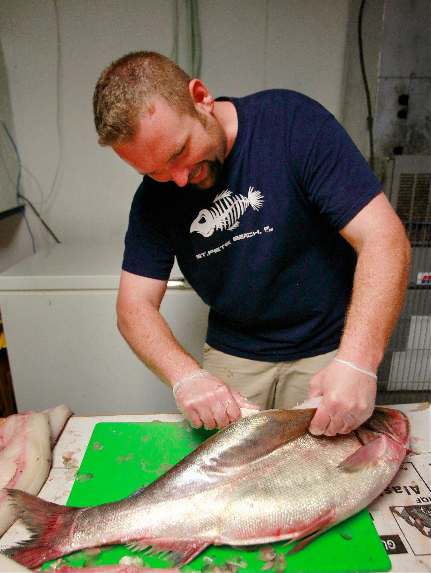 Clint Carter fillets a silver Asian carp, an invasive species that poses a threat to native fish in Illinois waterways, at Carter's Fish Market in Springfield.