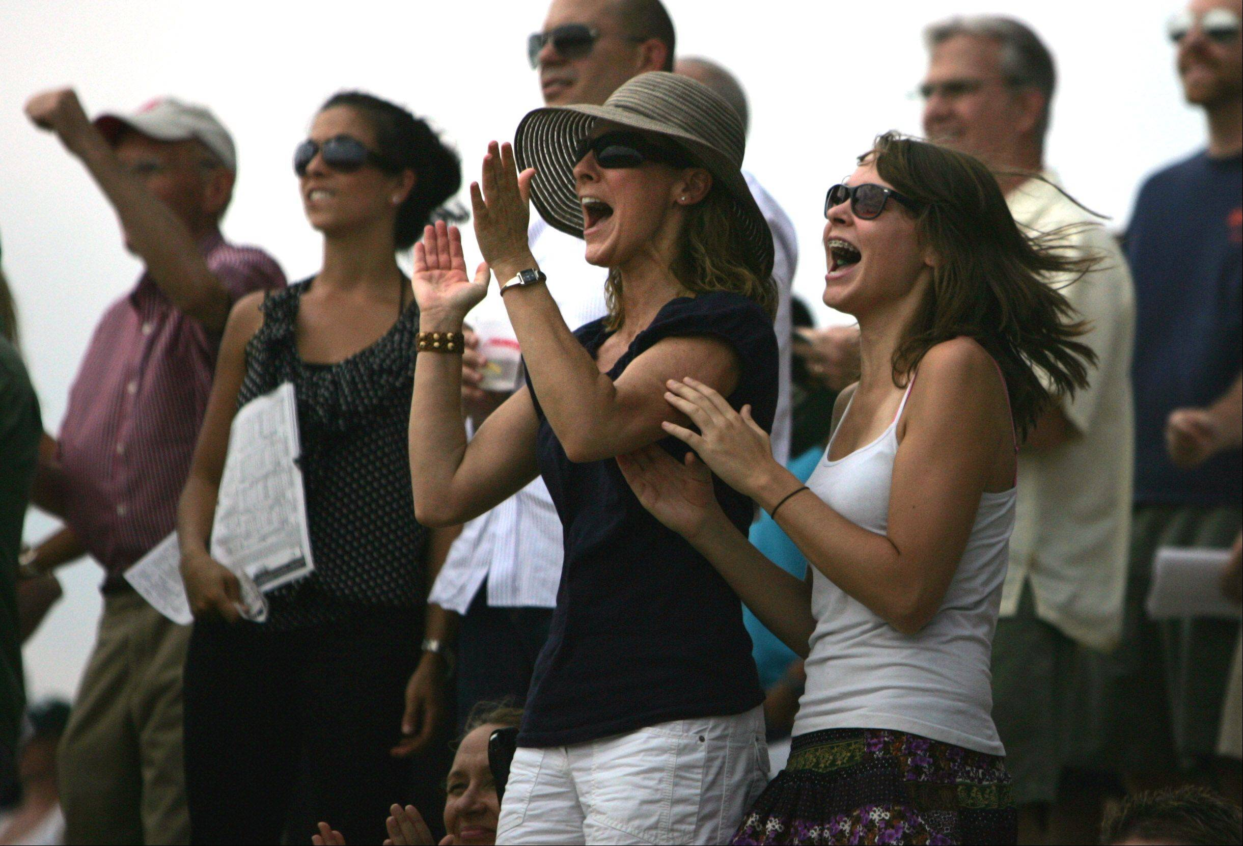 Race fans cheer for an early race during the day of racing at the 27th Arlington Million.