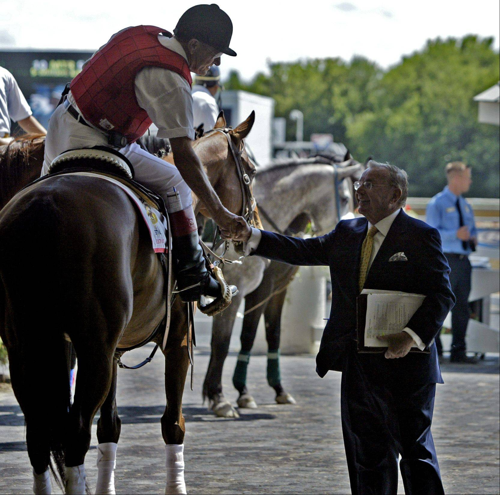 Arlington International Racecourse owner Richard Ducchossois shakes the hand of an outrider during the 22nd annual running of the Arlington Million.